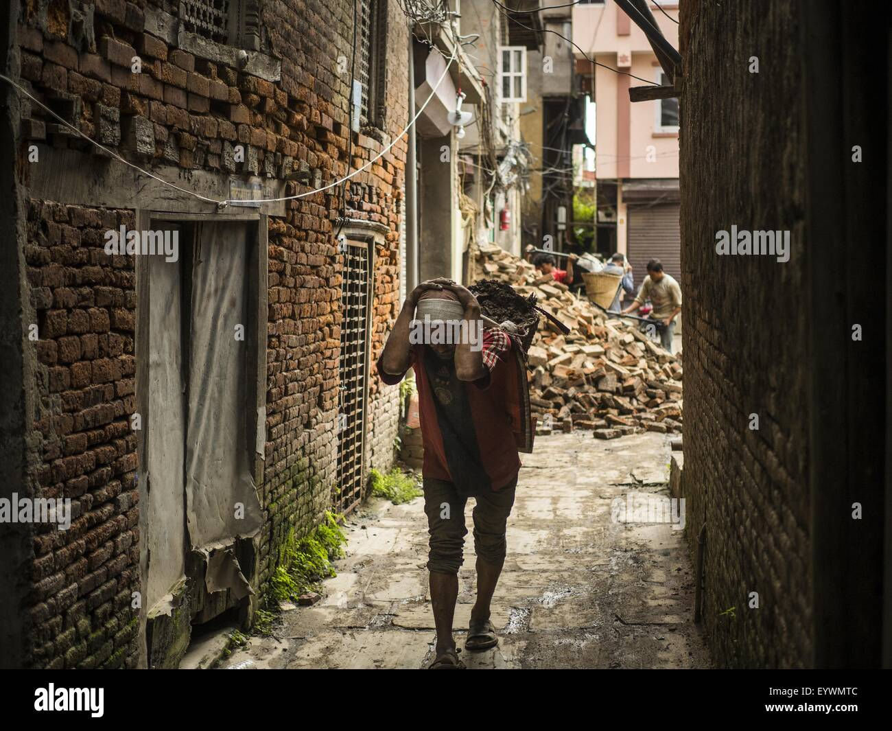 Kathmandu, Nepal. 1st Aug, 2015. A worker in Kathmandu carries bricks out of a home destroyed by the earthquake. - Stock Image