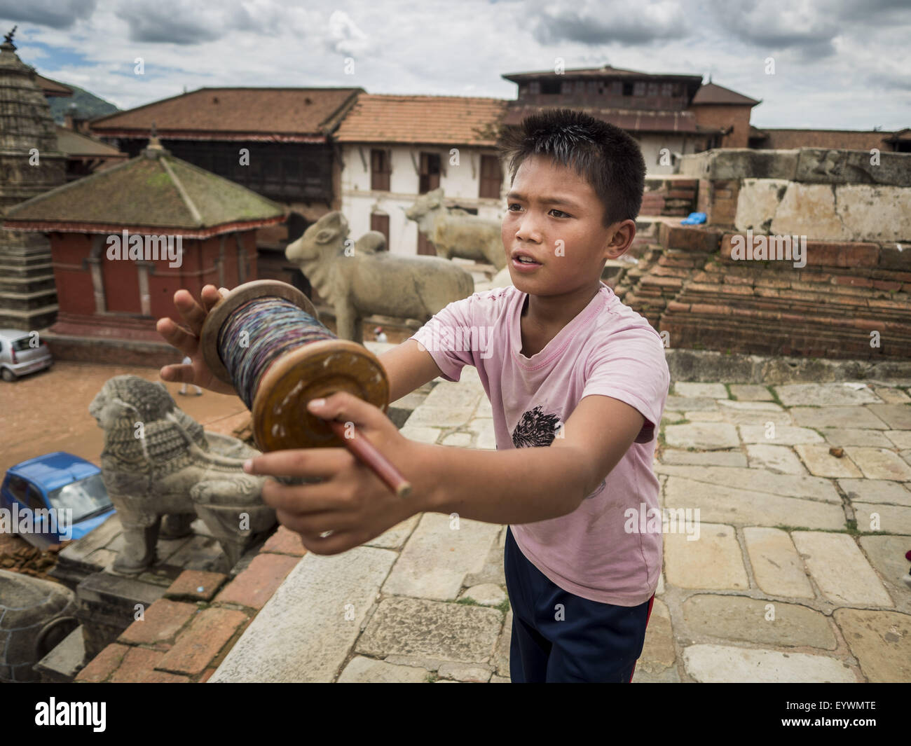 Bhaktapur, Central Region, Nepal. 2nd Aug, 2015. A boy flies his kite from the top of a temple destroyed by the - Stock Image
