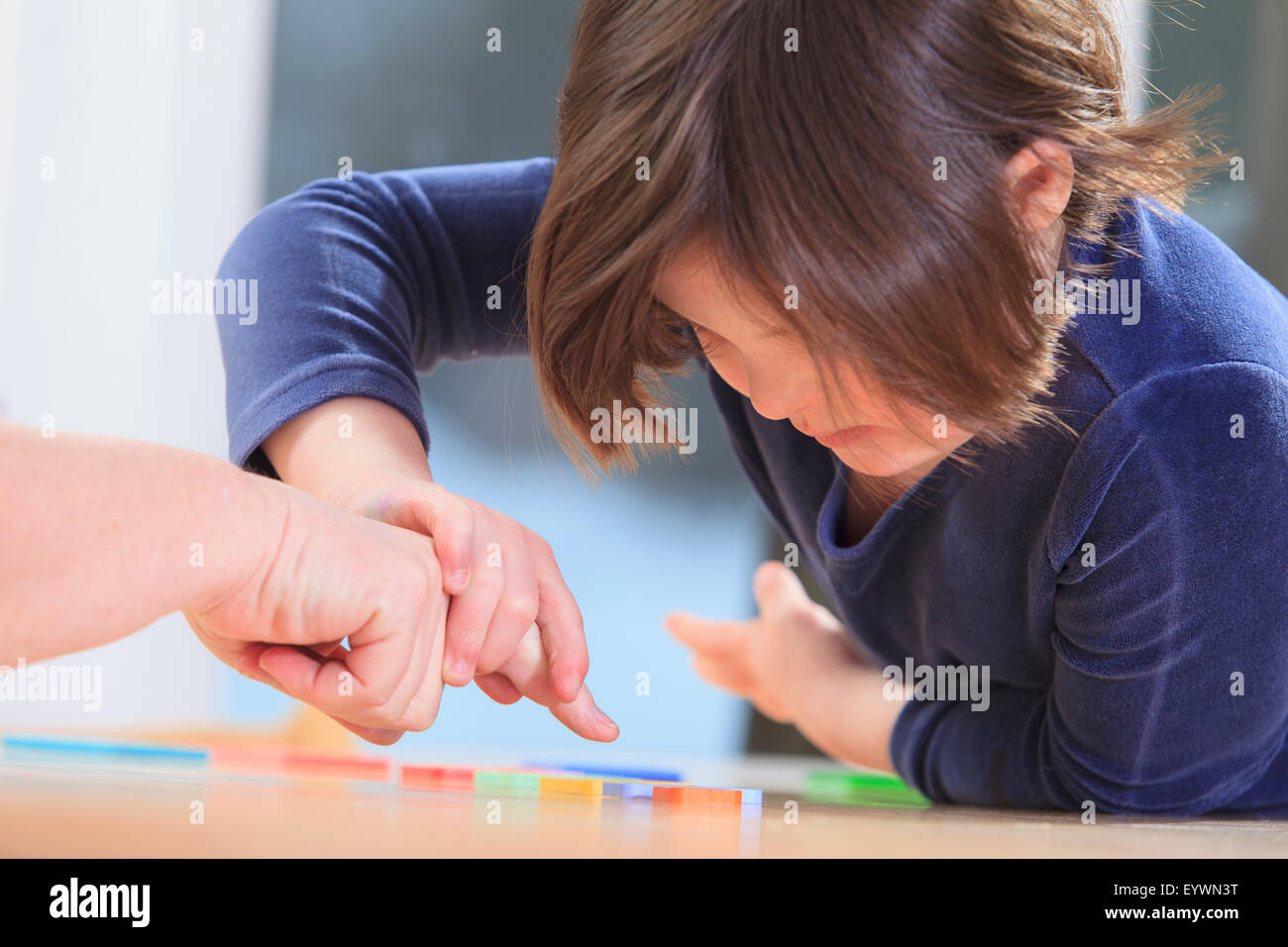 Little girl with Down Syndrome playing a learning game with her Mom - Stock Image