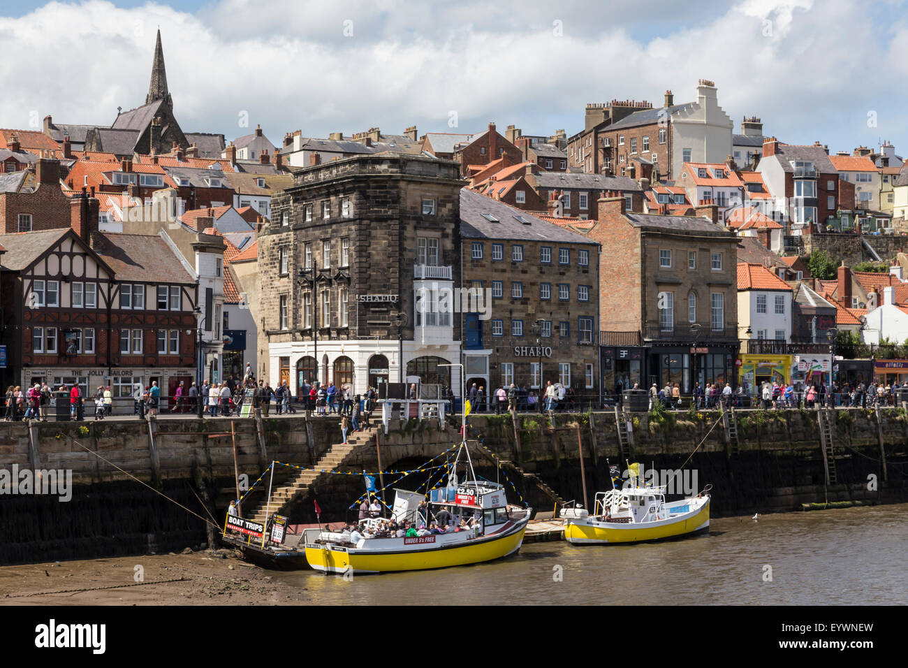 Boats moored on the West Side of the River Esk and passers-by on Pier Road, Whitby, North Yorkshire, Yorkshire, - Stock Image