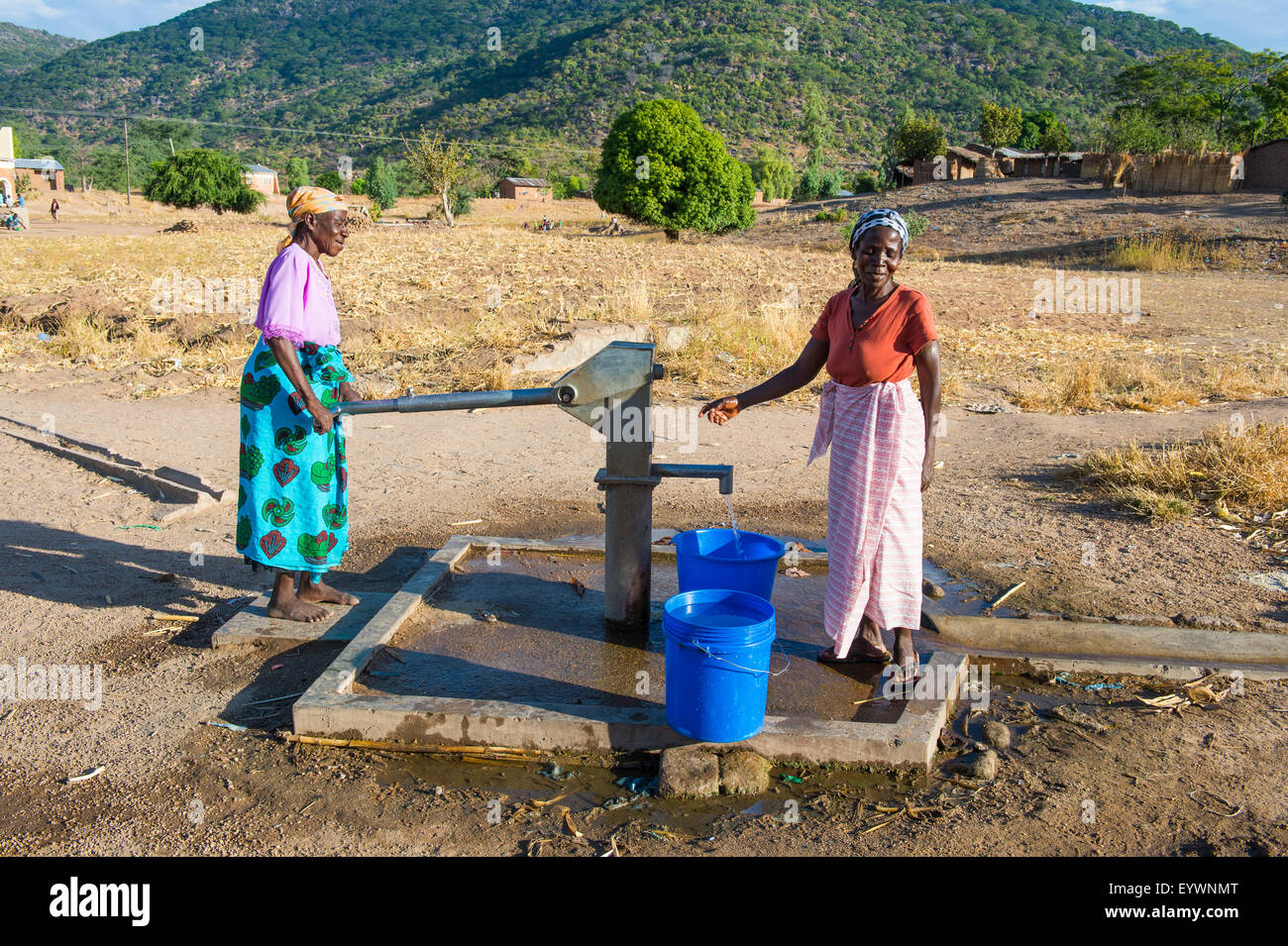 Women pumping water out of a well at Lake Malawi, Cape Maclear, Malawi, Africa - Stock Image