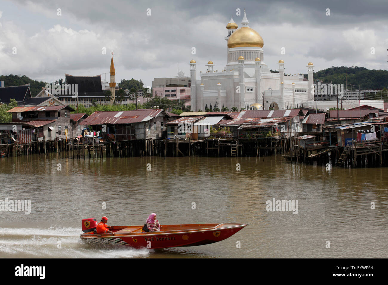 Boats past water village with Omar Ali Saifuddien mosque in Bandar Seri Begawan, Brunei, Southeast Asia, Asia - Stock Image