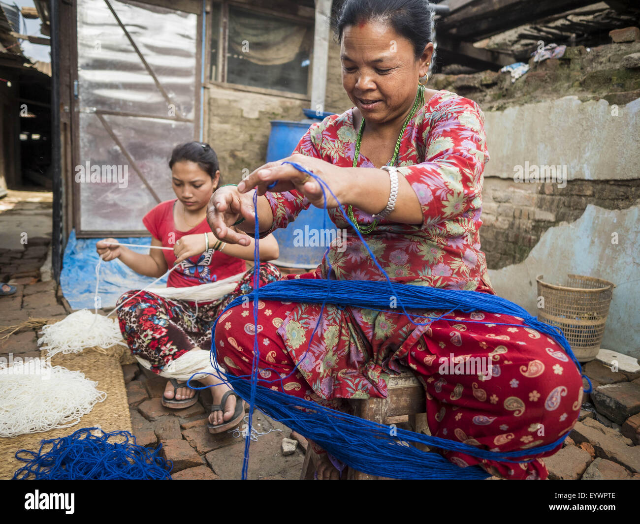 Bhaktapur, Central Region, Nepal. 2nd Aug, 2015. Women make tourist curios in front of their temporary shelters - Stock Image