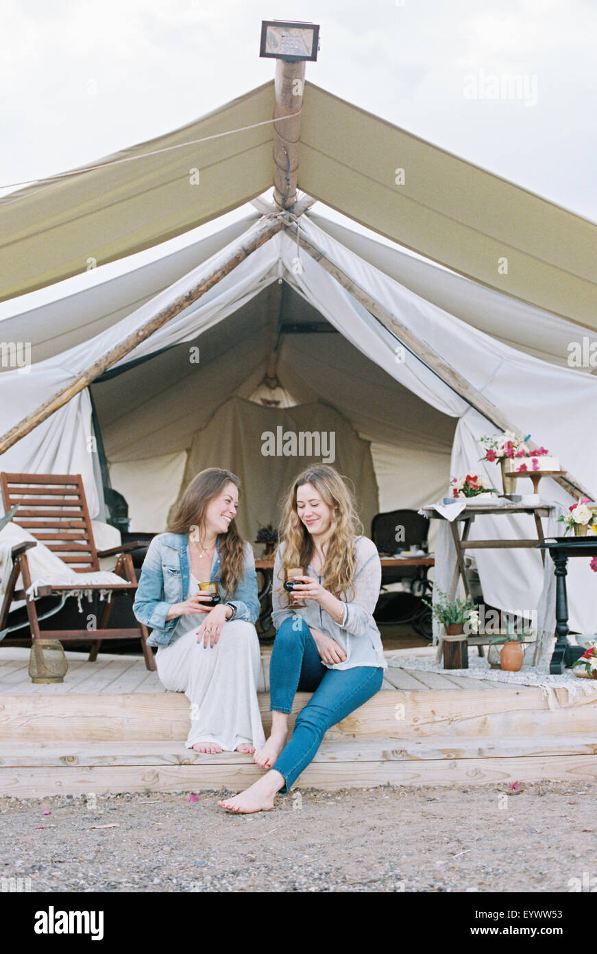Two smiling women sitting outside a large tent laughing and having a glass of wine. - Stock Image