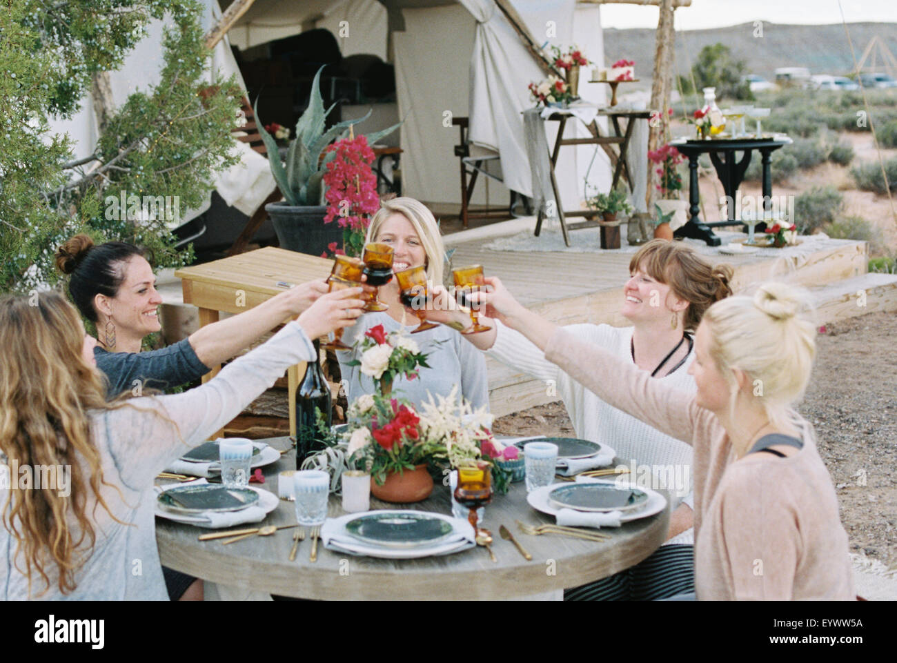 A group of women enjoying an outdoor meal by a large tent, in a desert landscape, raising a toast by clinking glasses. - Stock Image