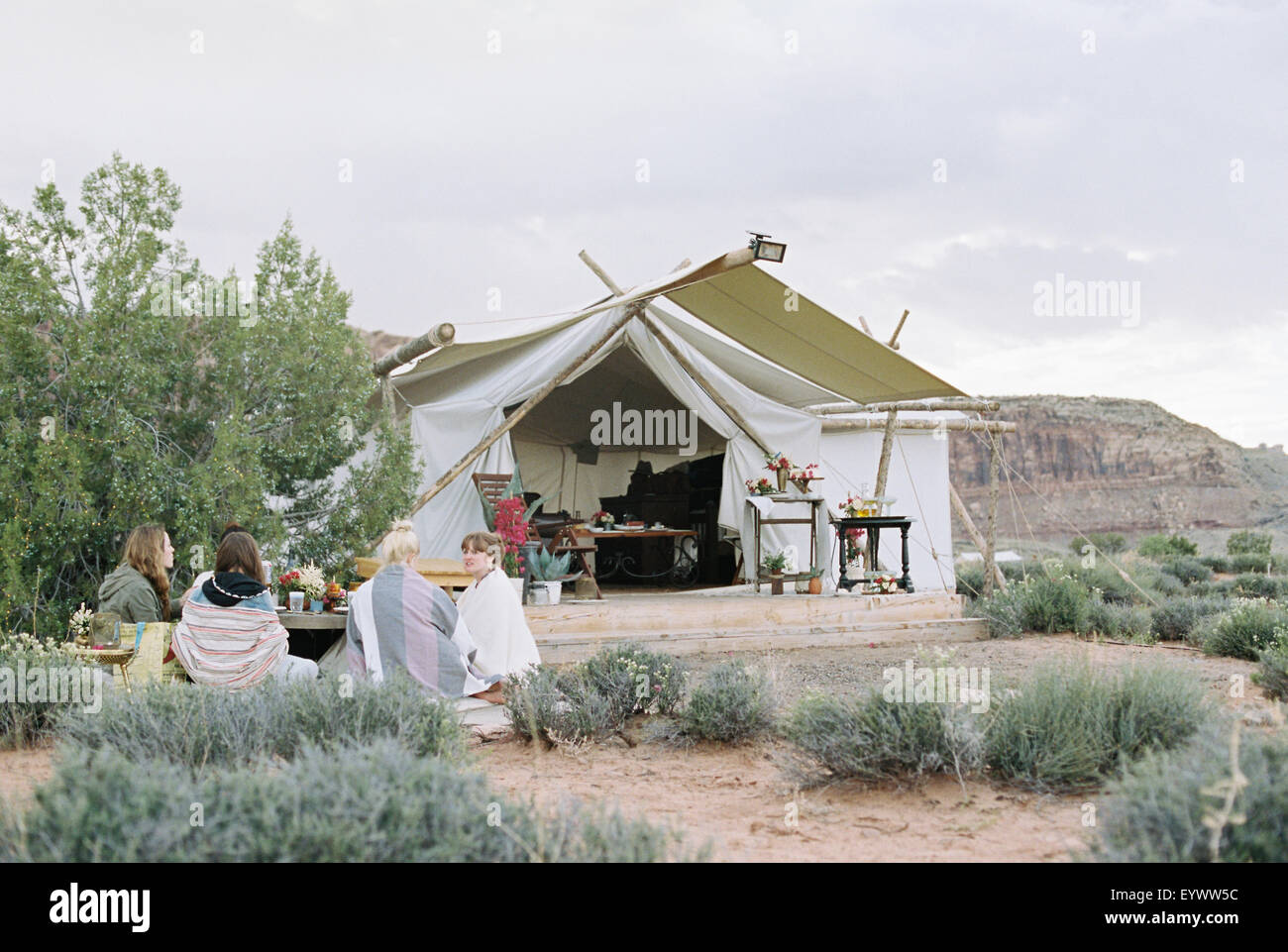 Group of women friends enjoying an outdoor meal in a desert by a large tent. - Stock Image