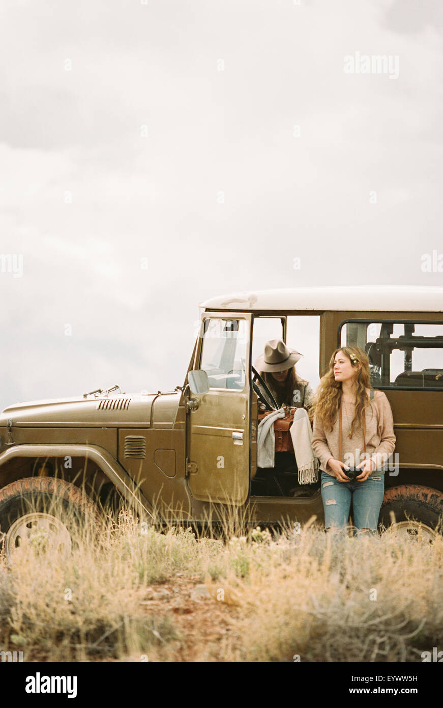 Two women by a 4x4 in a desert, taking a break from the road. - Stock Image