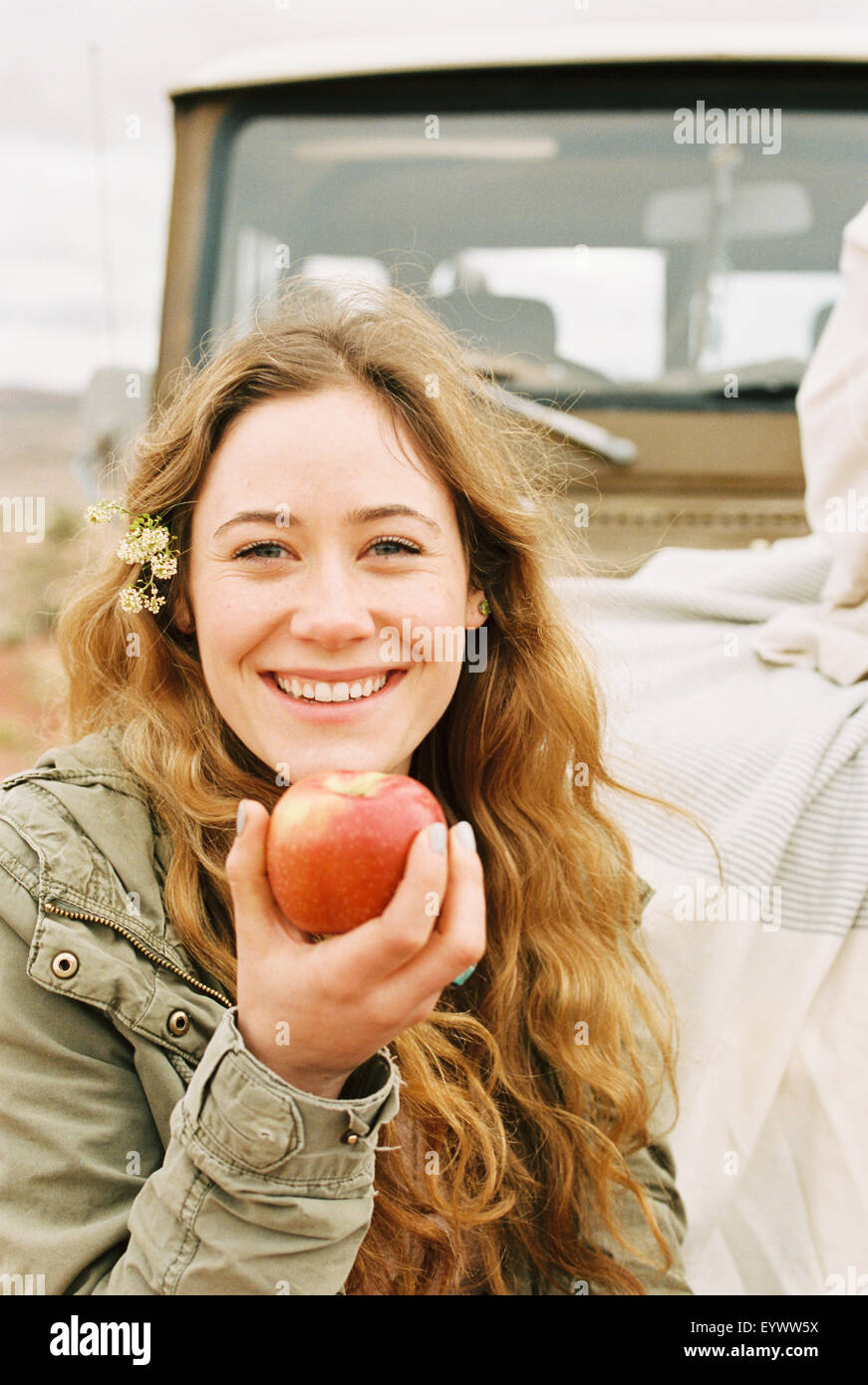 A young woman holding out a red skinned apple. - Stock Image