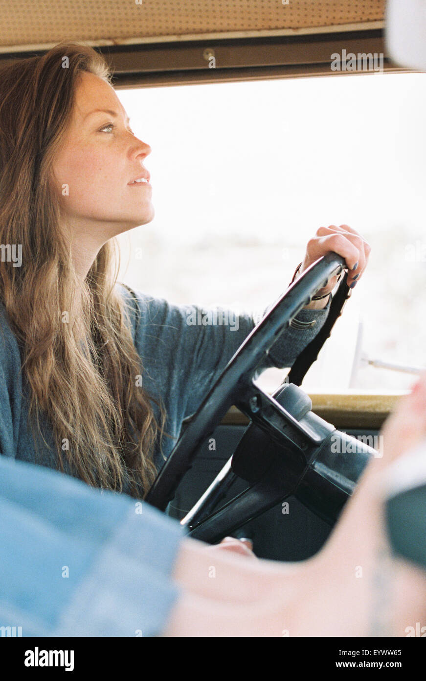 Barefoot woman resting her feet on the dashboard of a 4x4, a tattoo on her right foot, another woman driving. - Stock Image