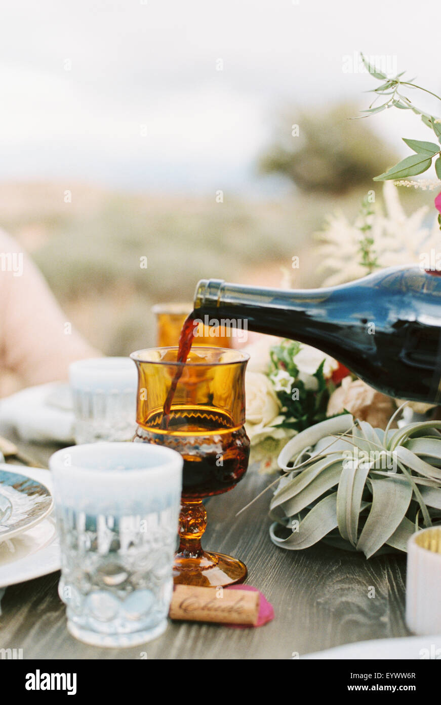 An outdoor meal in a desert, red wine being poured into a glass. - Stock Image