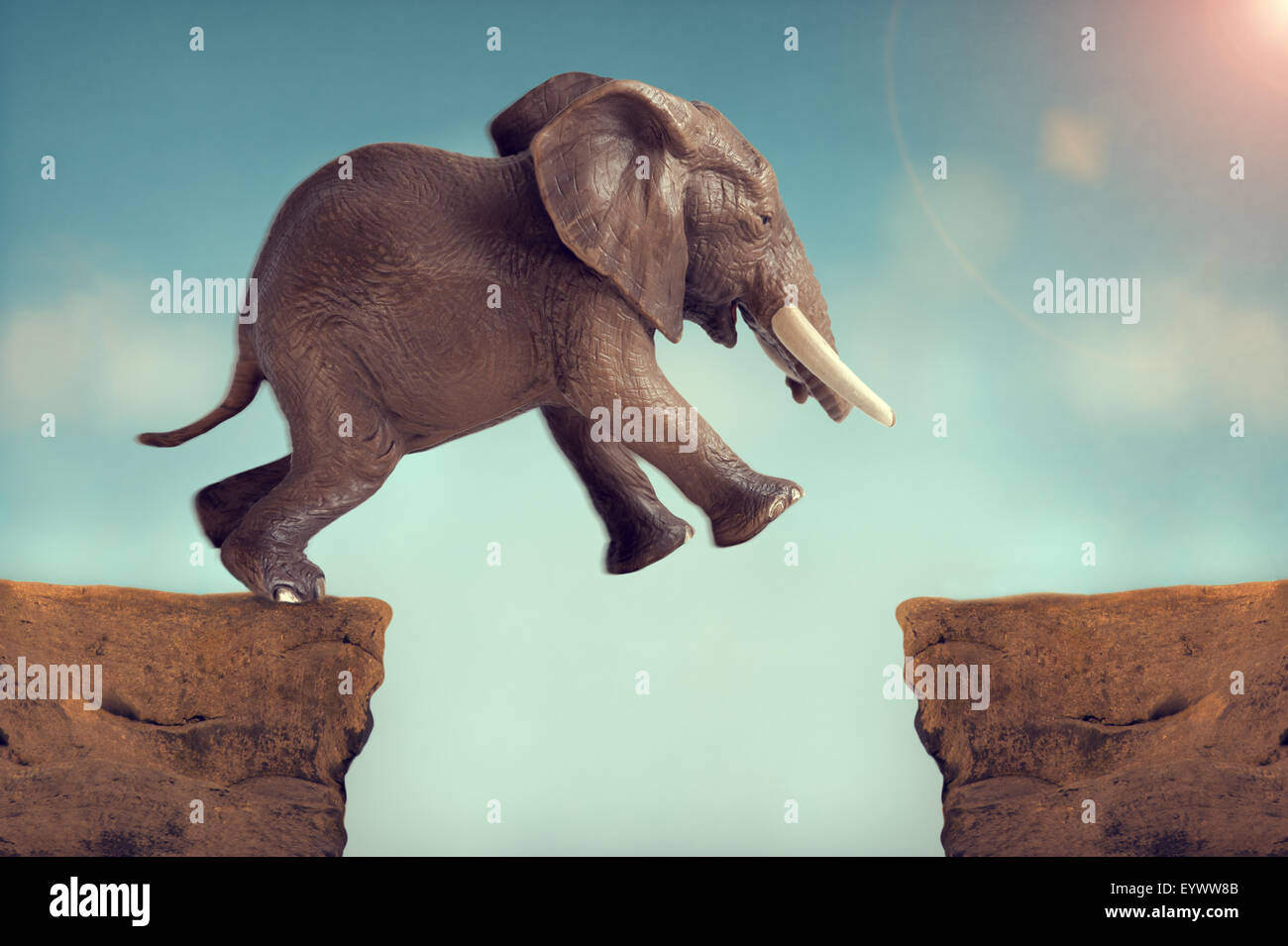 leap of faith concept elephant jumping across a crevasse - Stock Image
