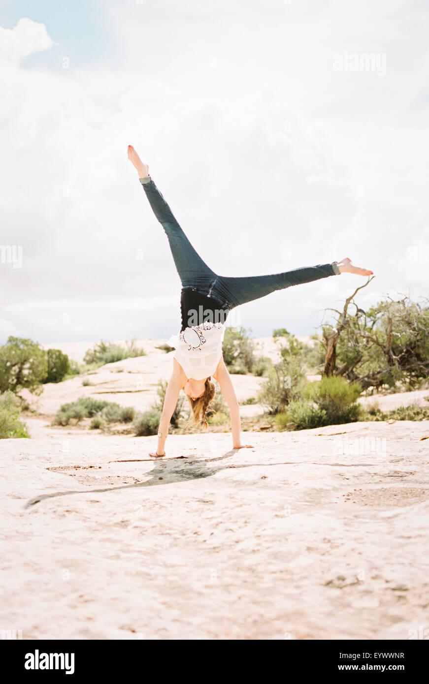 Barefoot woman wearing jeans, cartwheeling - Stock Image