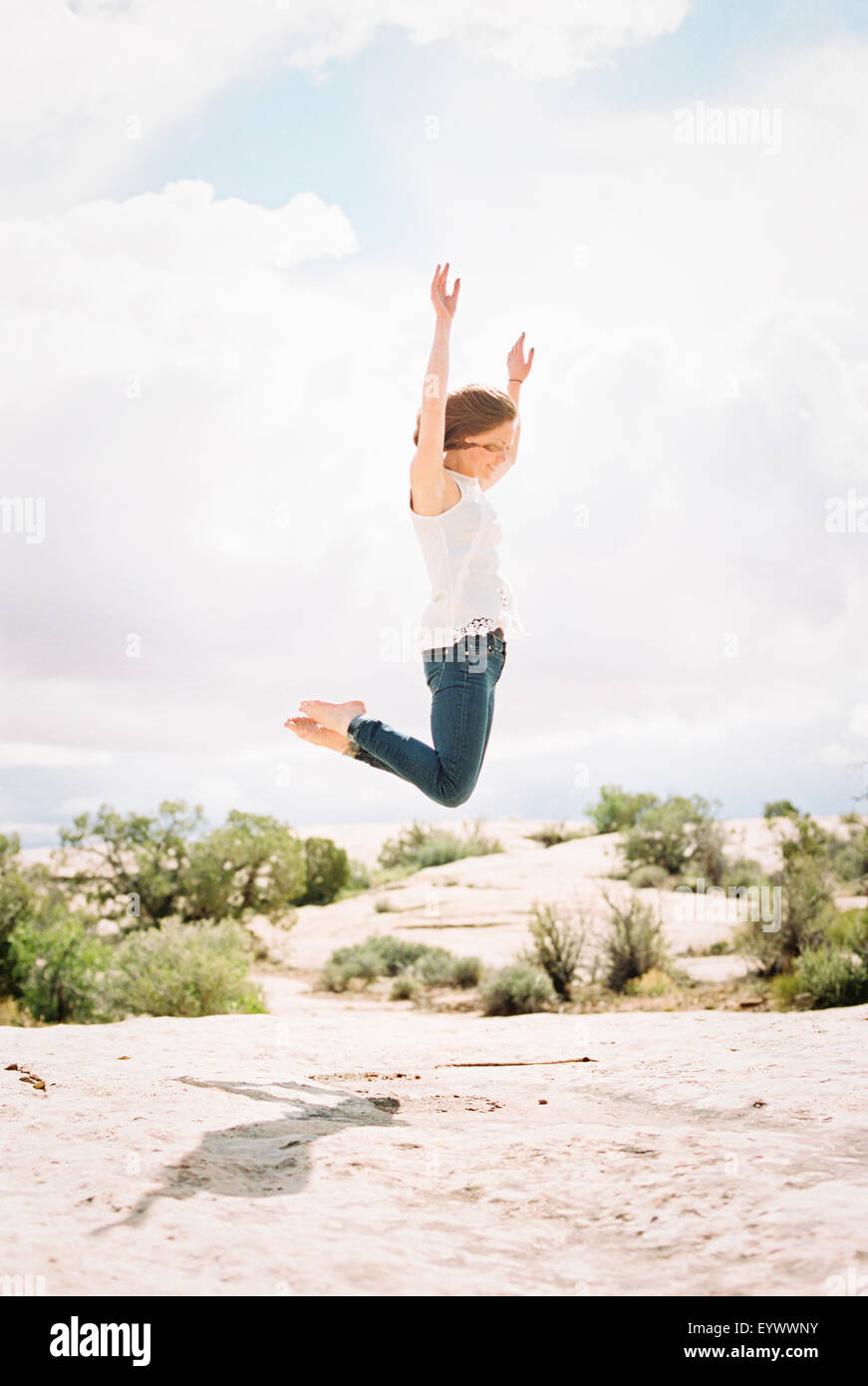 Barefoot woman jumping up in the air - Stock Image