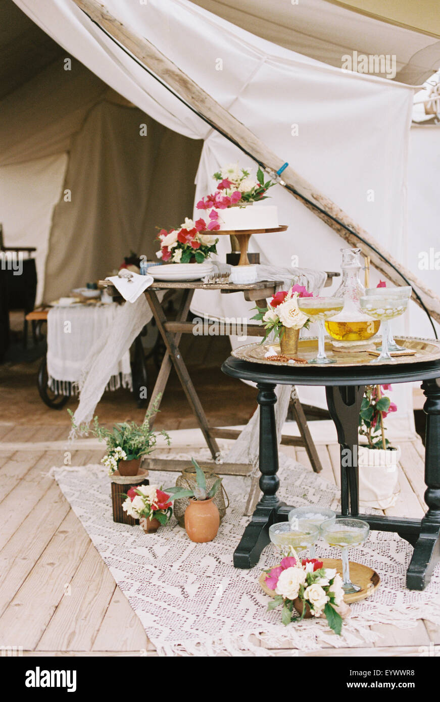 Food and drink on tables outside tent in a desert. - Stock Image