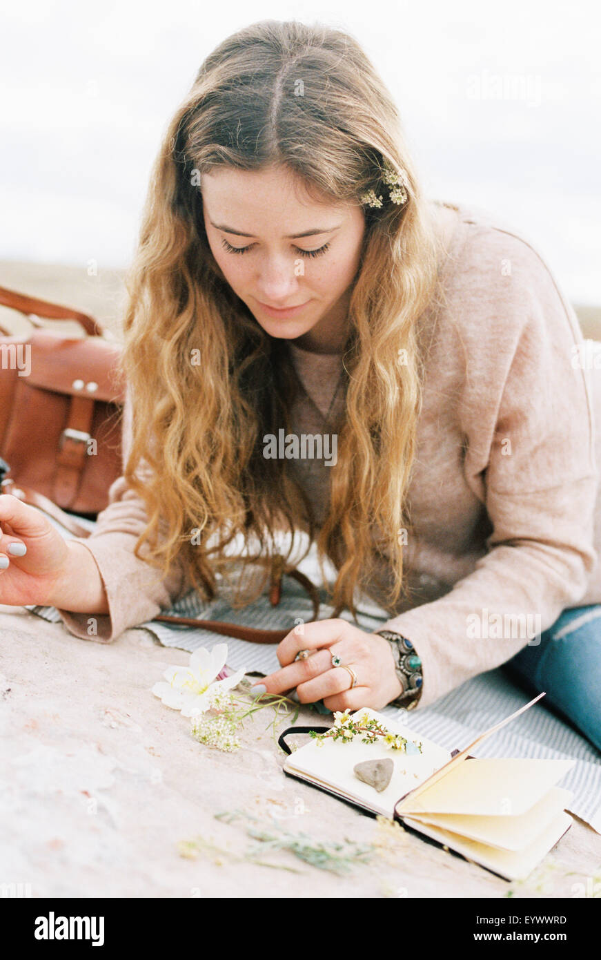 Woman putting flowers between the pages of book. - Stock Image