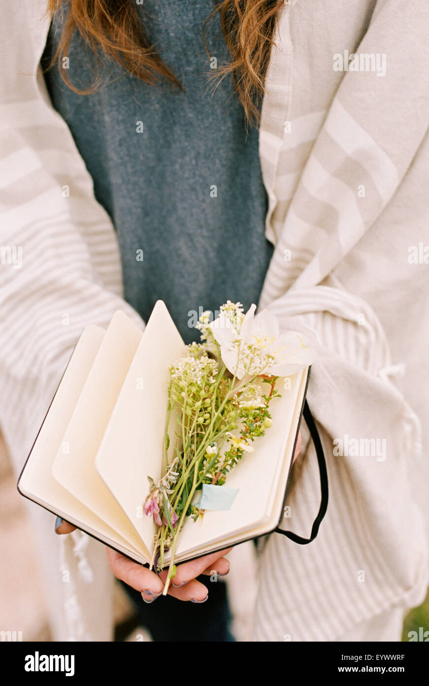 woman with notebook flowers between pages - Stock Image