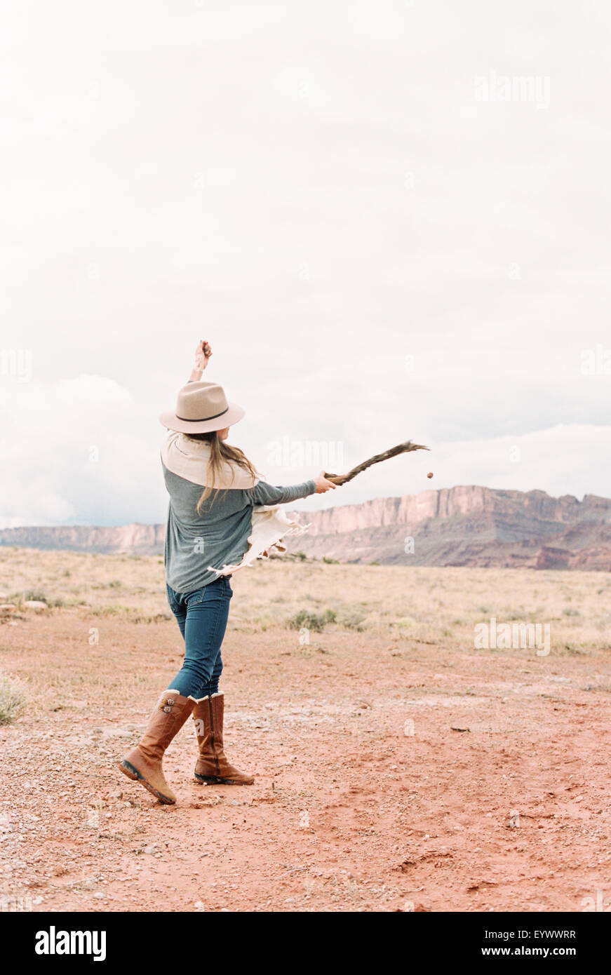 woman hitting a stone with stick - Stock Image