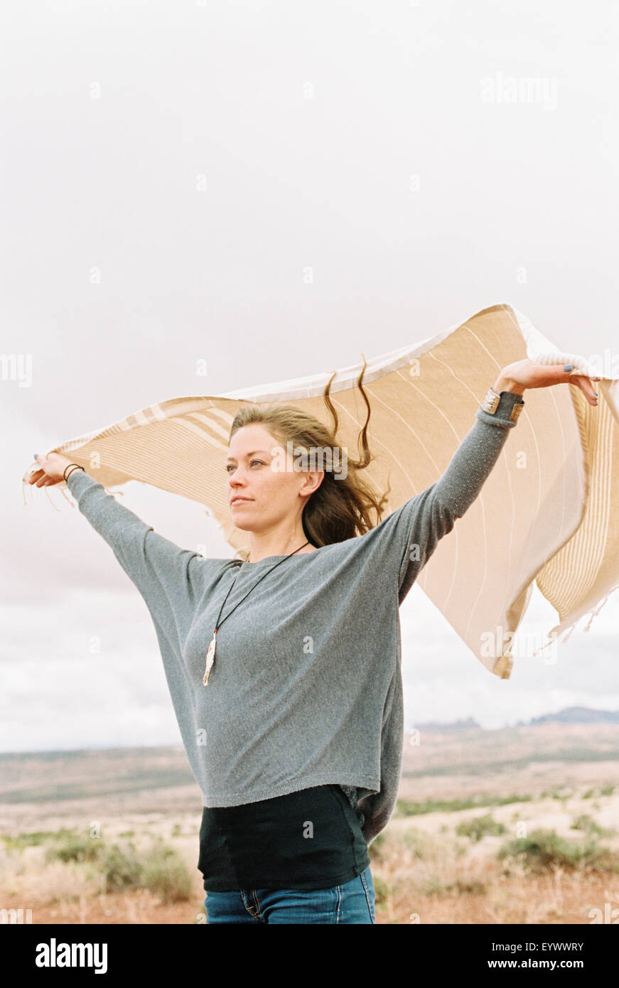 Woman holding a wrap fluttering in the wind. - Stock Image