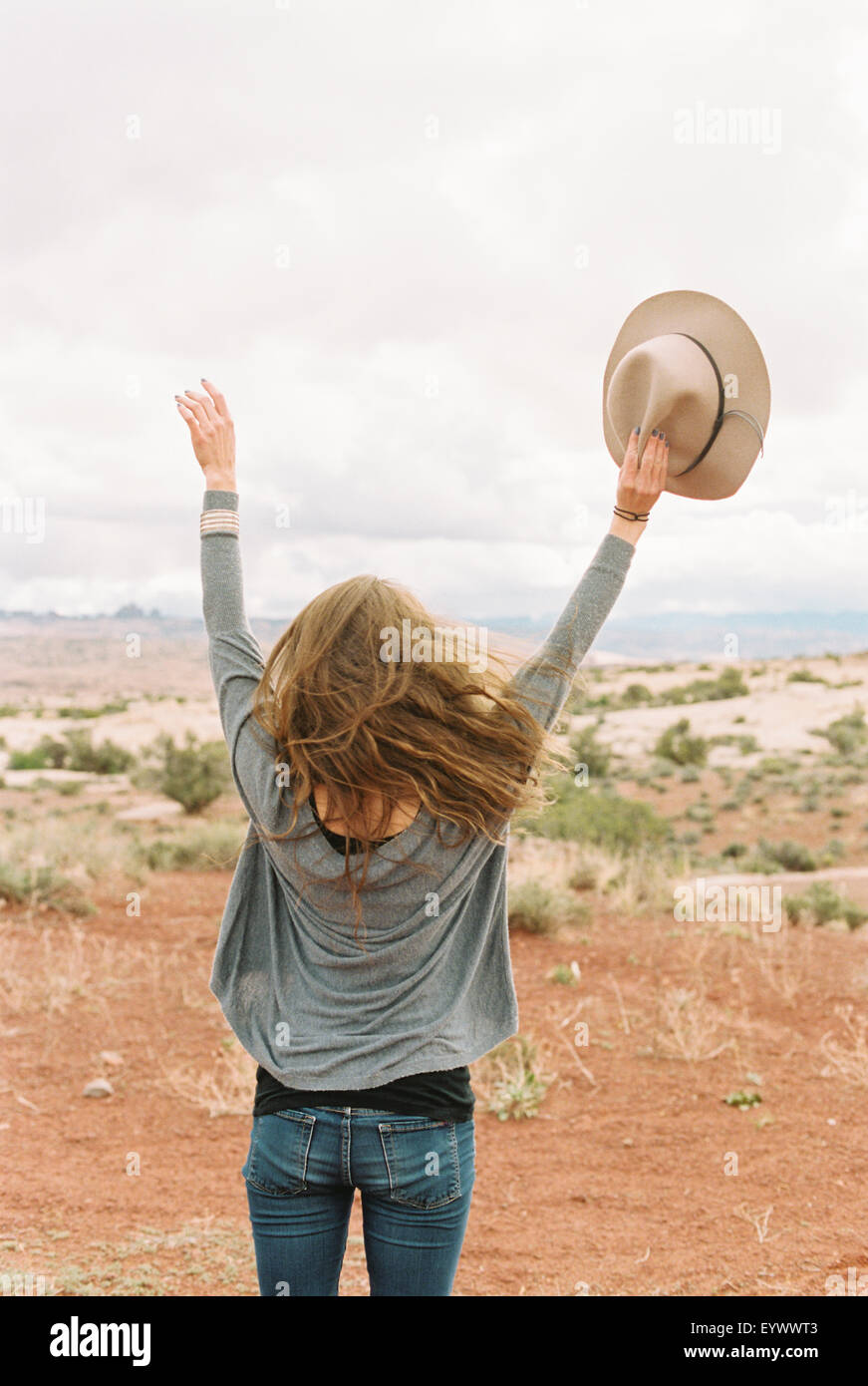 woman standing her arms raised up in the air. - Stock Image