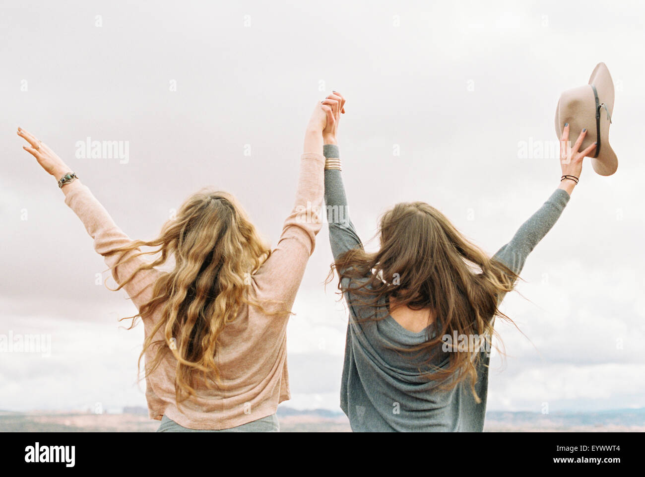 two women with their arms raised up in the air. - Stock Image