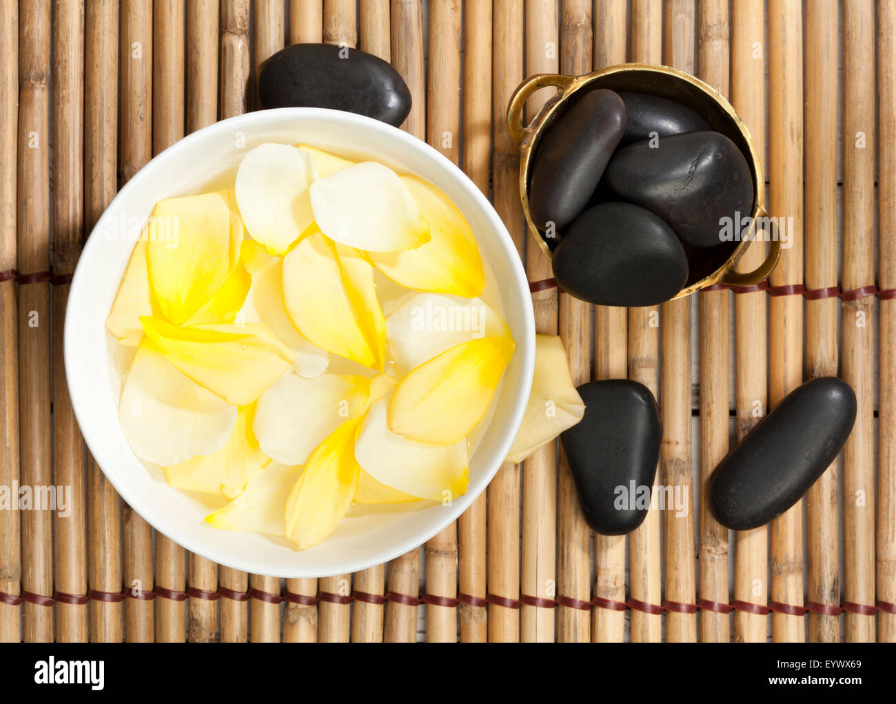 yellow rose petals in bowl of water and lastone therapy pebbles on bamboo mat, top view - Stock Image