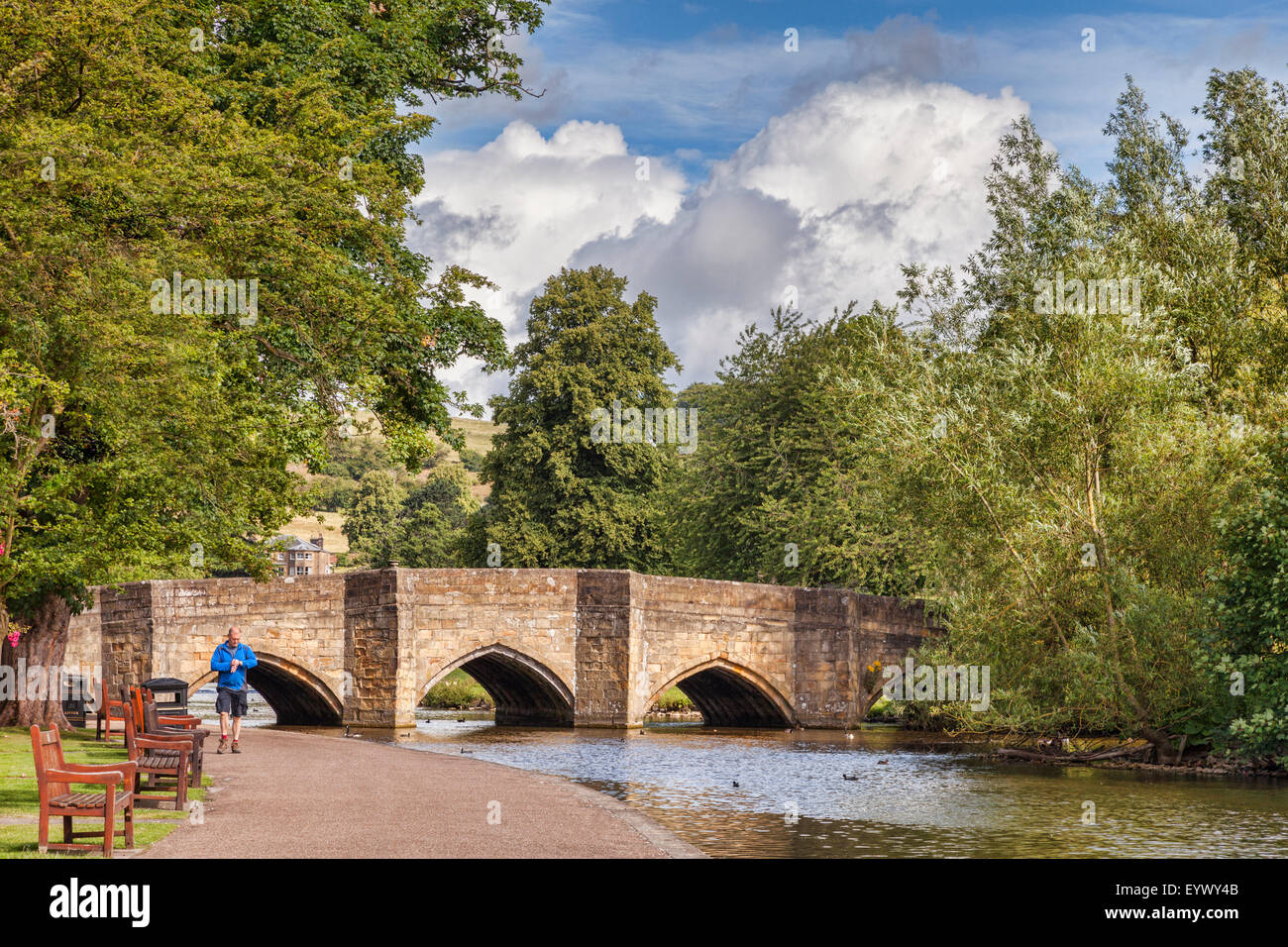 A man looking at his watch as he walks beside the River Wye, in front 5 arch bridge built 700 years ago, Bakewell, - Stock Image