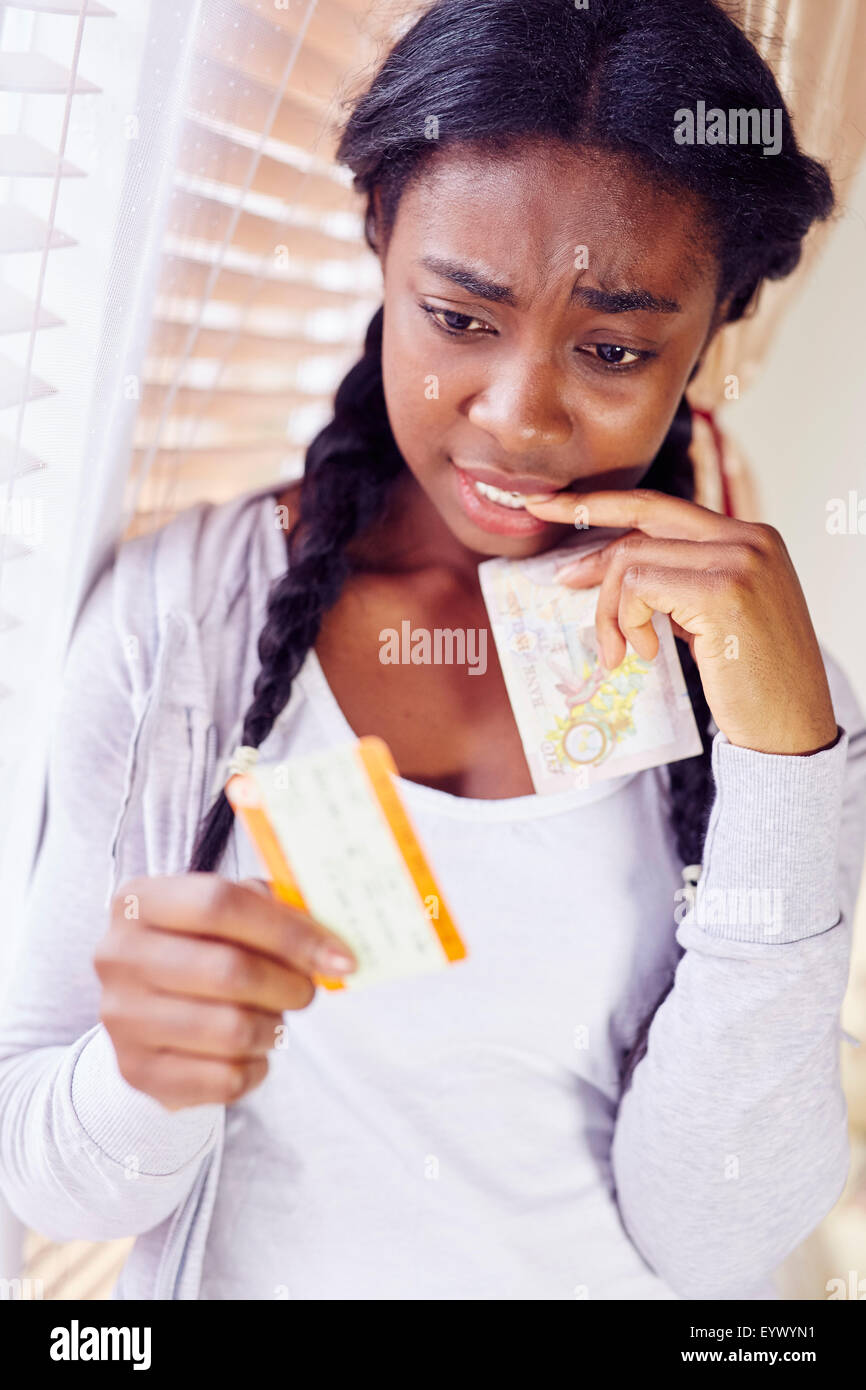 Girl worried about expensive train tickets - Stock Image