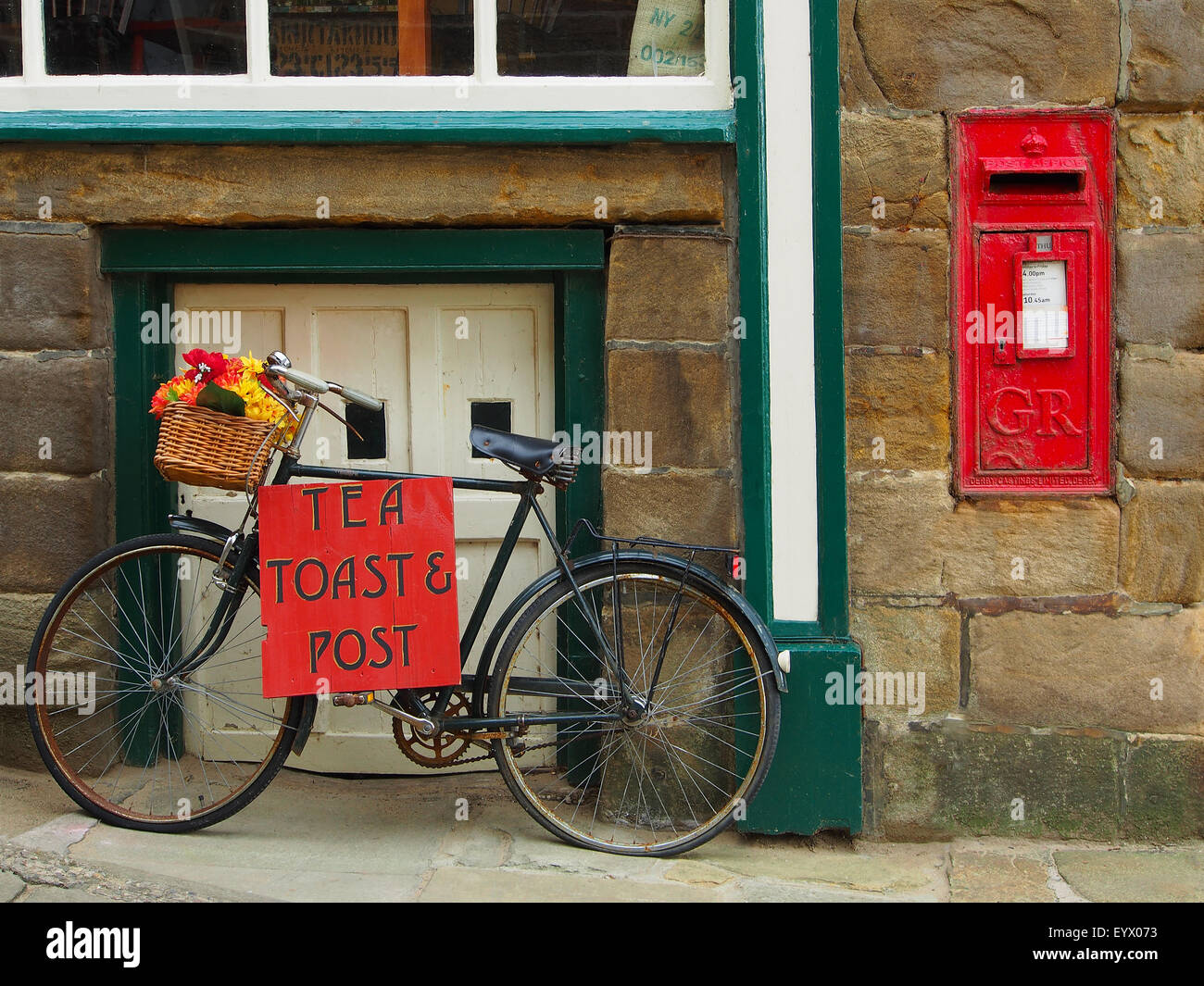 Bicycle sign advertising Tea, Toast and Post outside a cafe at Robin Hoods Bay Near Whitby on the Yorkshire coast Stock Photo