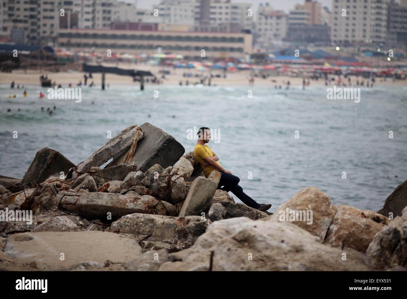 Gaza City, Gaza Strip, Palestinian Territory. 4th Aug, 2015. A Palestinian man sits on the coast of the Mediterranean - Stock Image