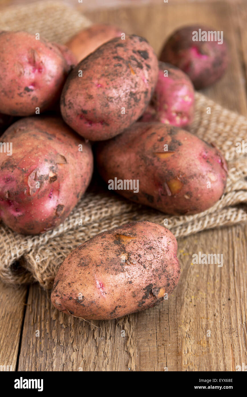 Raw organic potatoes over burlap and rustic wooden table - Stock Image