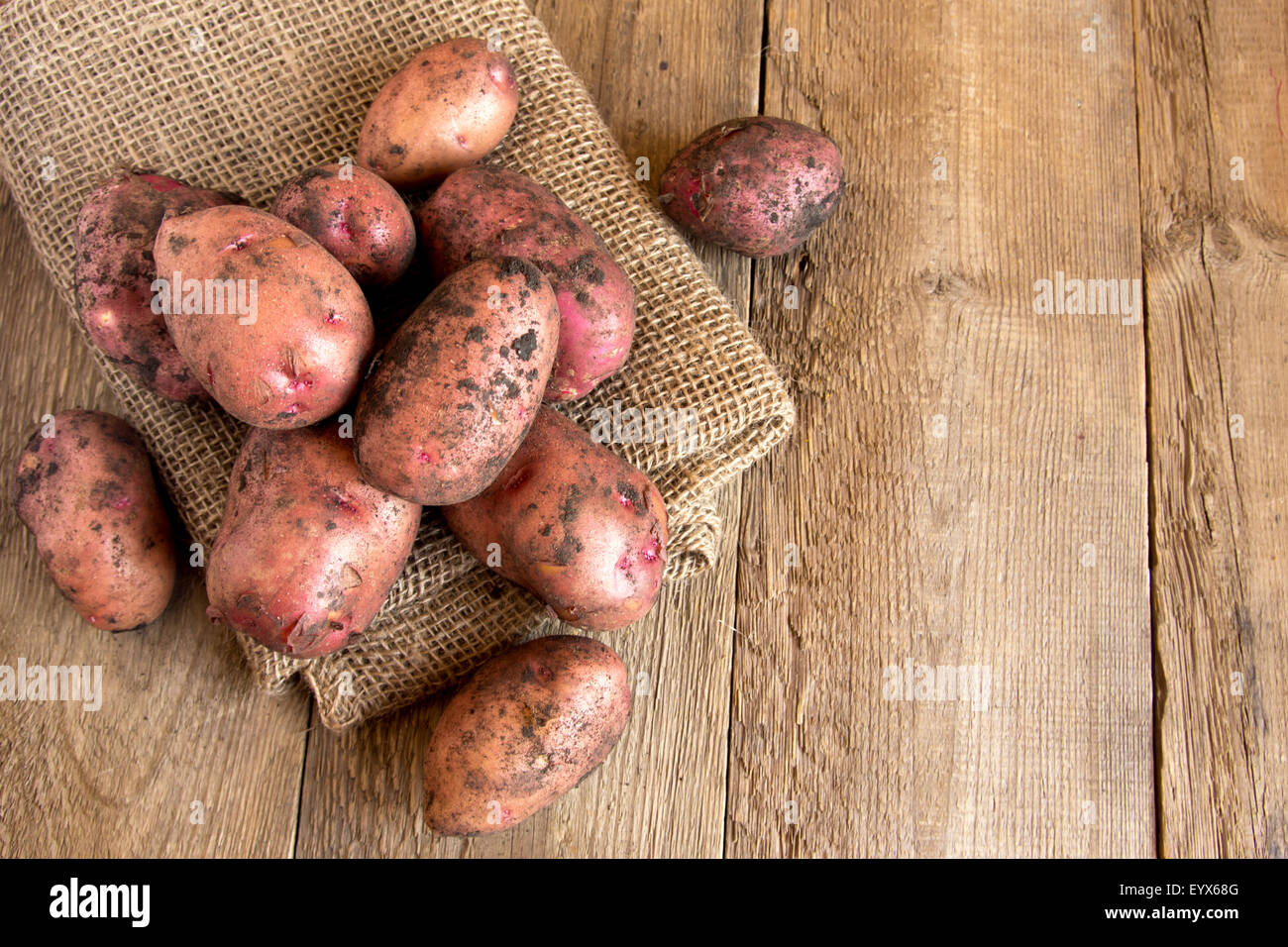 Raw organic potatoes over burlap and rustic wooden table, copy space - Stock Image