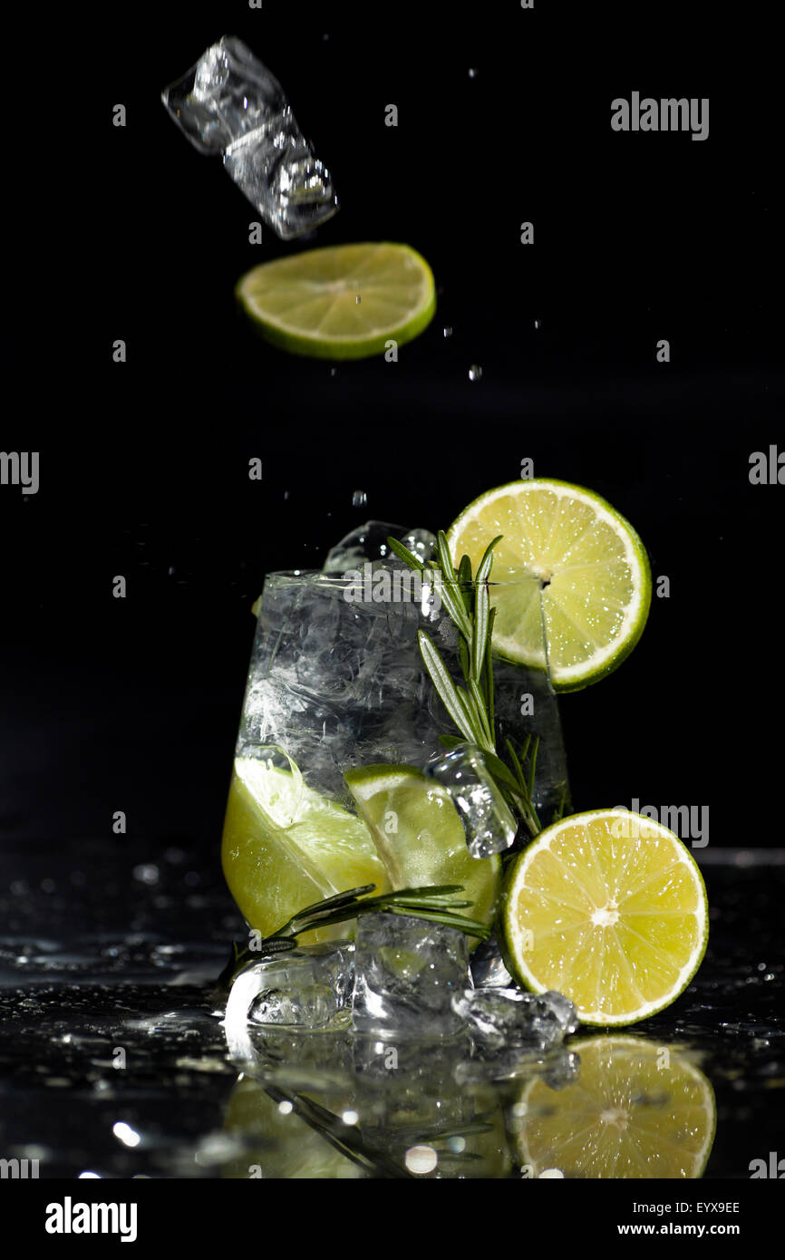 Glass with alcoholic drink with lime and ice on a black background. - Stock Image