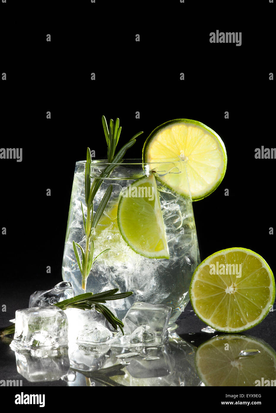 Glass with alcoholic drink with lime and ice on a black background. Stock Photo