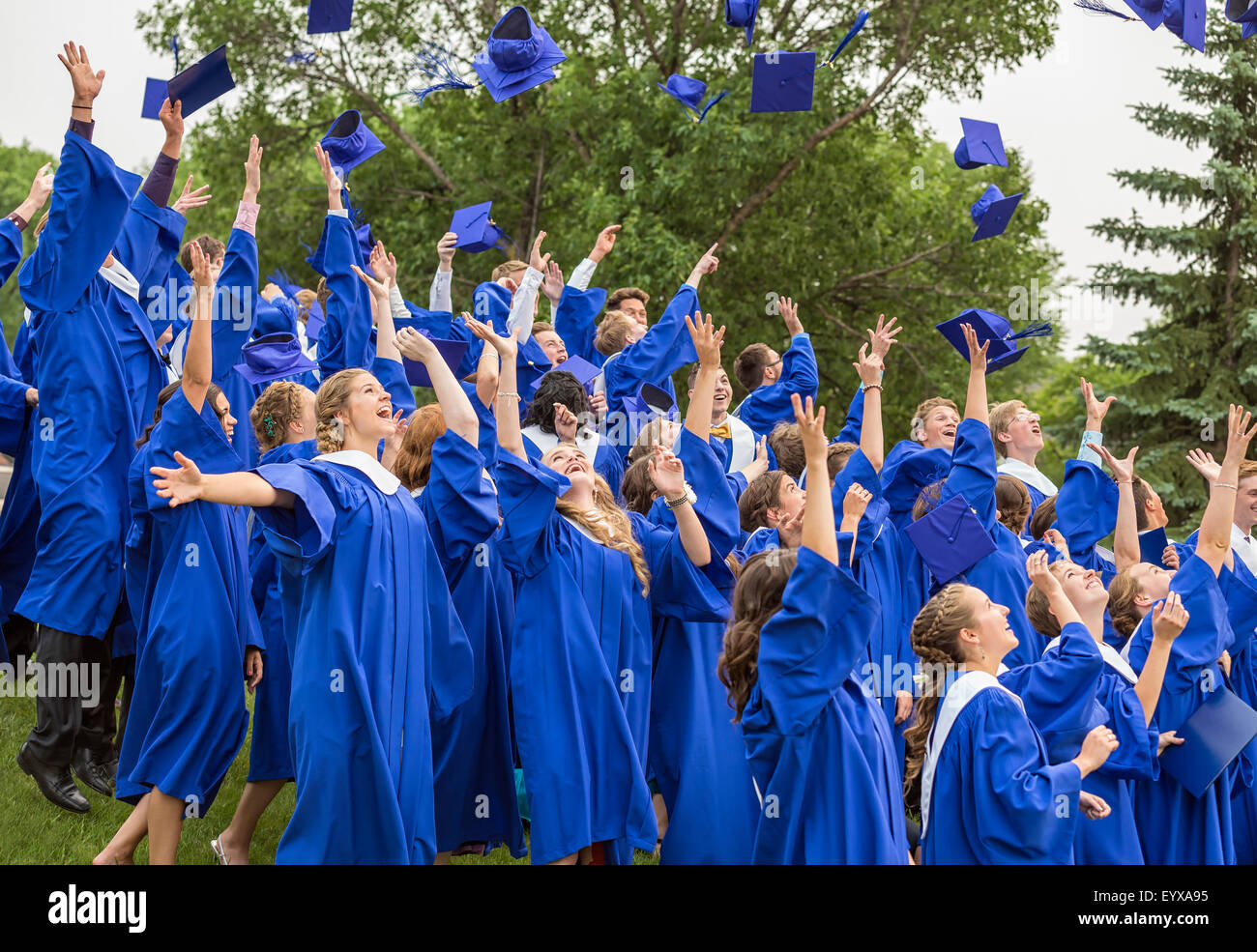 Graduates tossing caps in air, at a high school graduation ceremony. - Stock Image