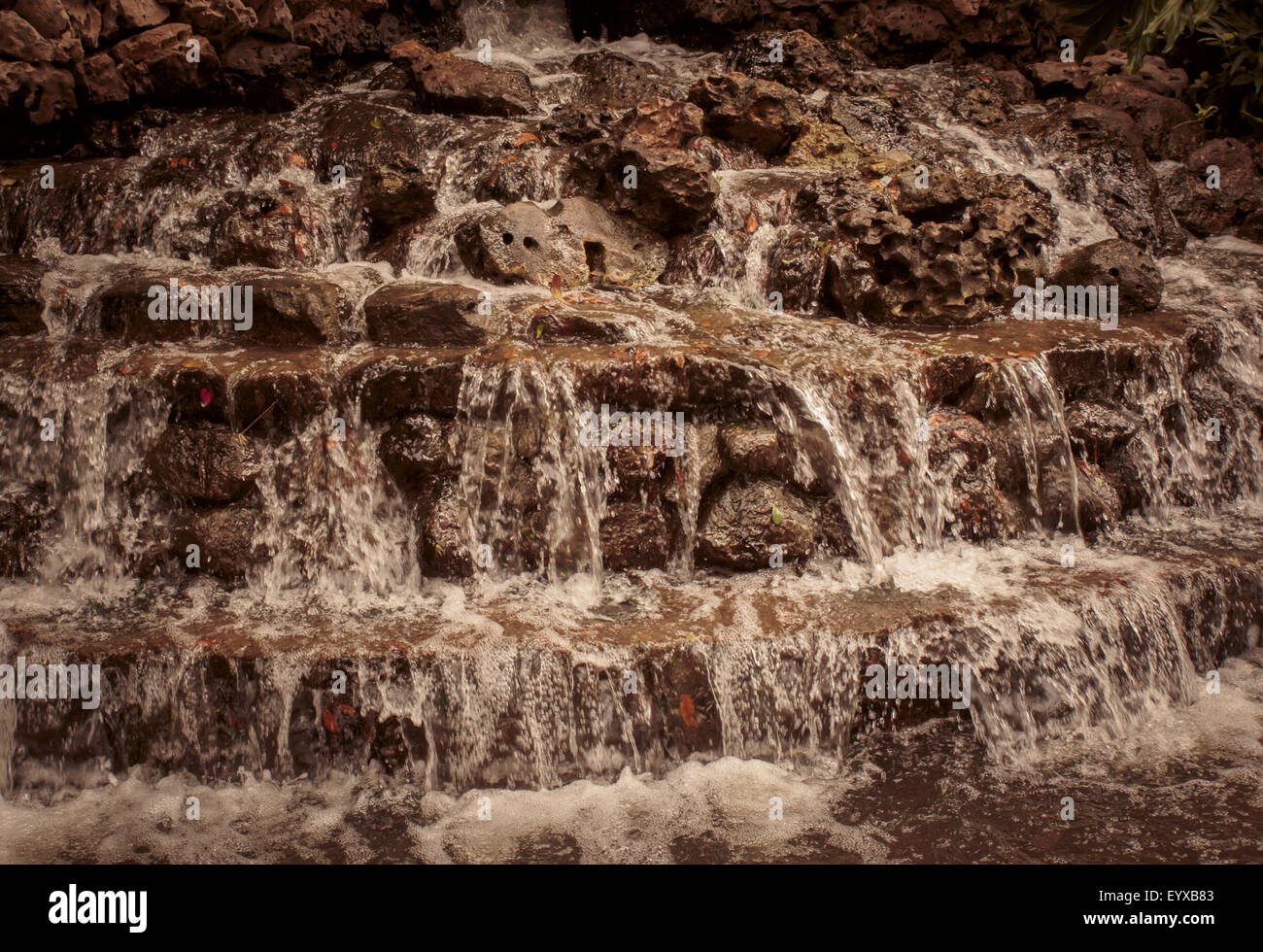 Water gently cascading over layers of rocks into a shallow pond; in sepia tones Stock Photo