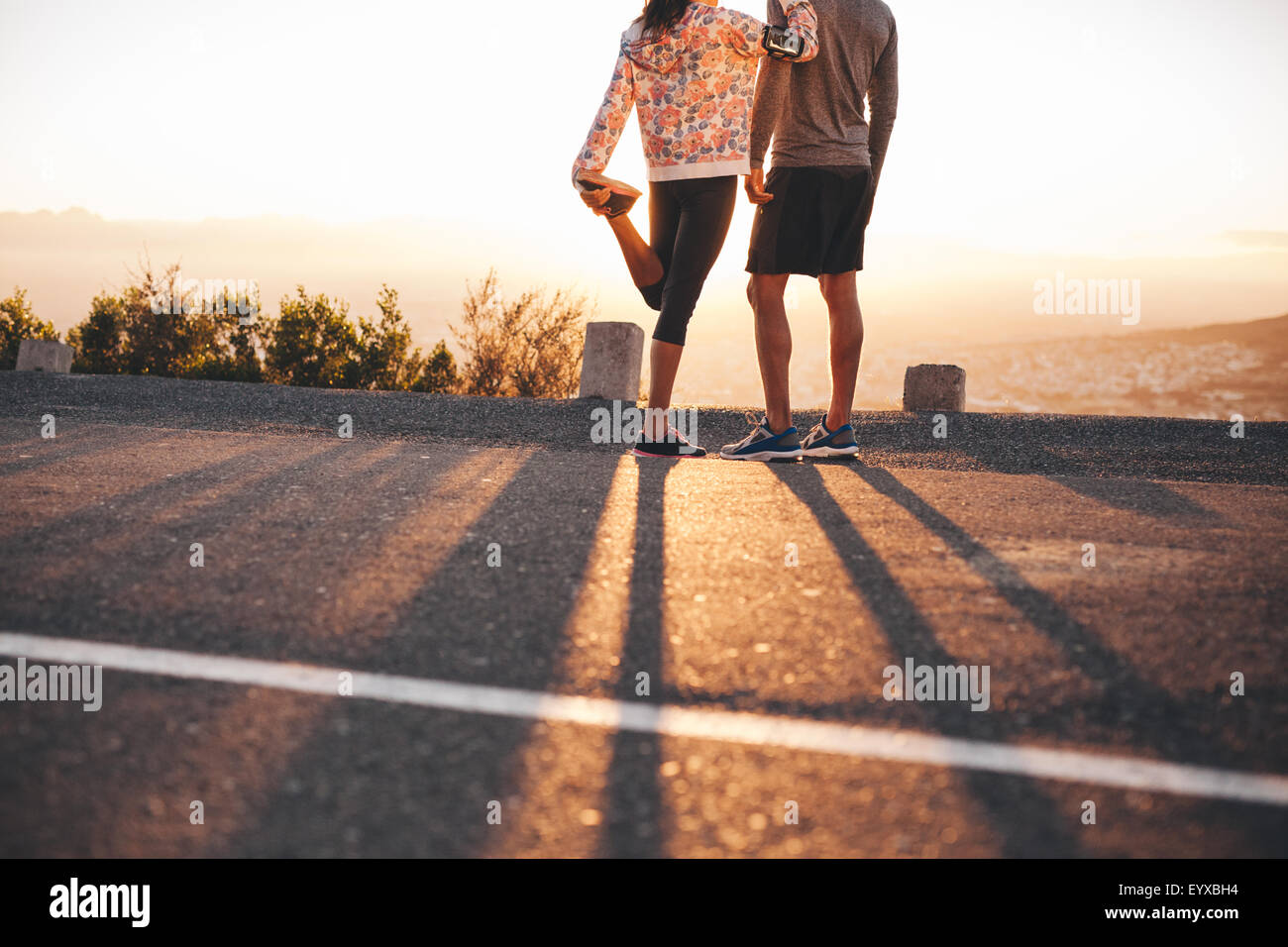 Cropped shot of man and woman standing on hillside road in morning. Woman stretching her leg. Couple of joggers - Stock Image