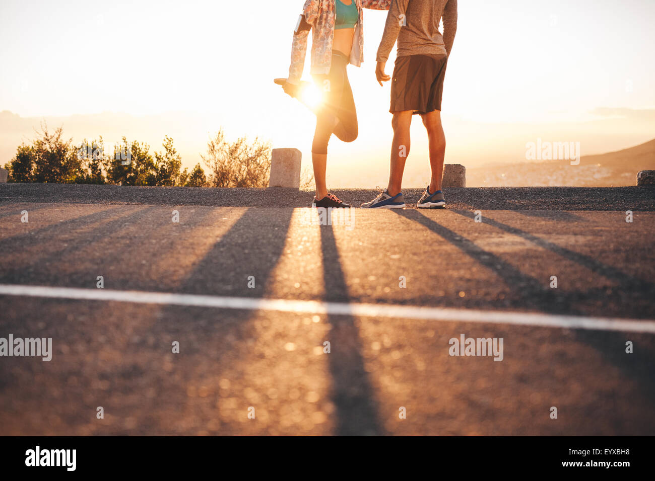 Cropped shot of fit young couple warming up before a run together at sunrise. Young man and woman exercising in - Stock Image