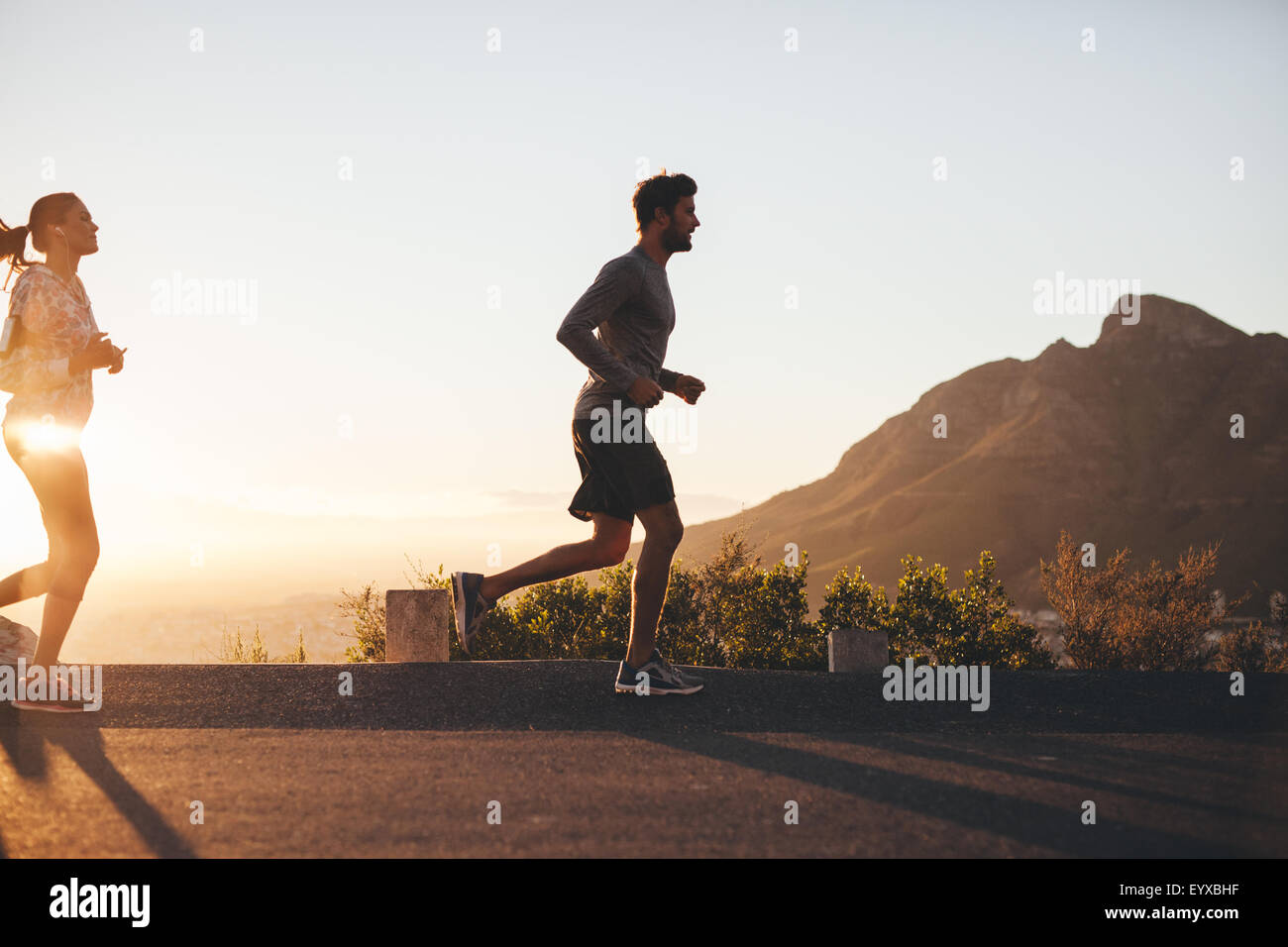 Outdoor shot of young couple on morning run. Young man and woman jogging on road outside during sunrise. Stock Photo