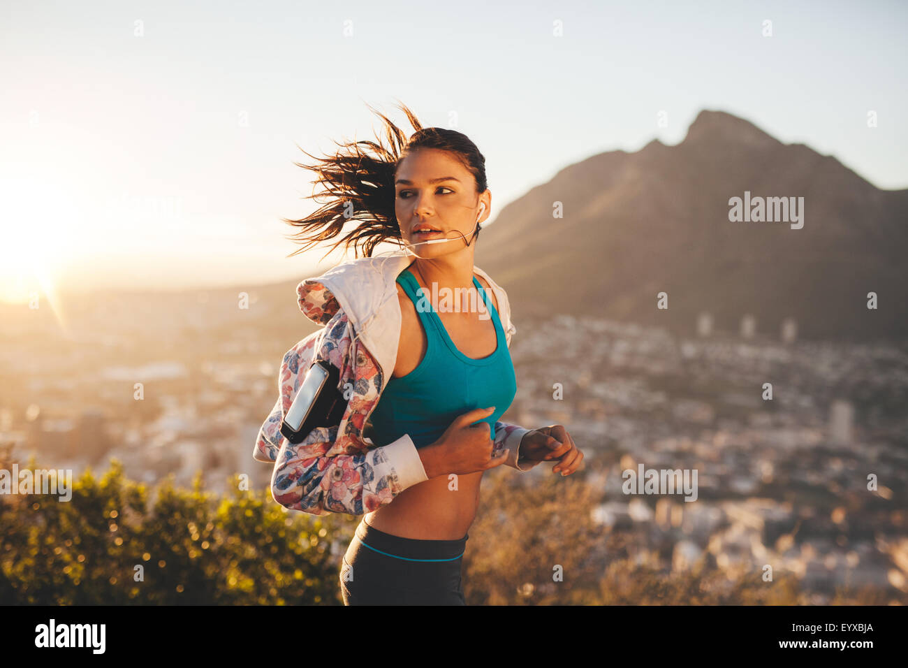 Female runner running outdoor in nature. Young woman jogging in morning looking over shoulder. - Stock Image