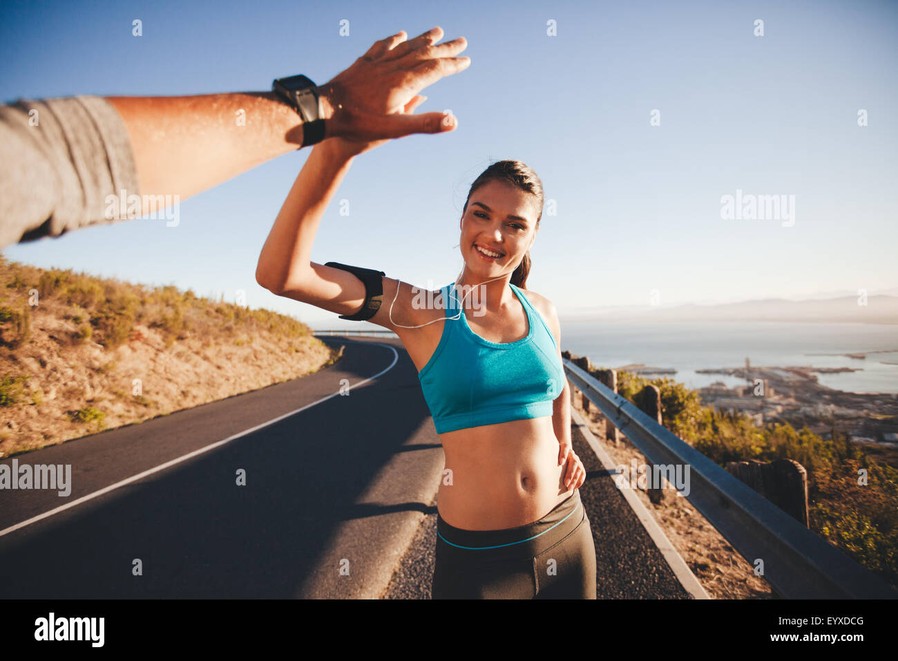 Fit young woman giving high five to her boyfriend after a run. POV shot of couple high fiving on country road in - Stock Image