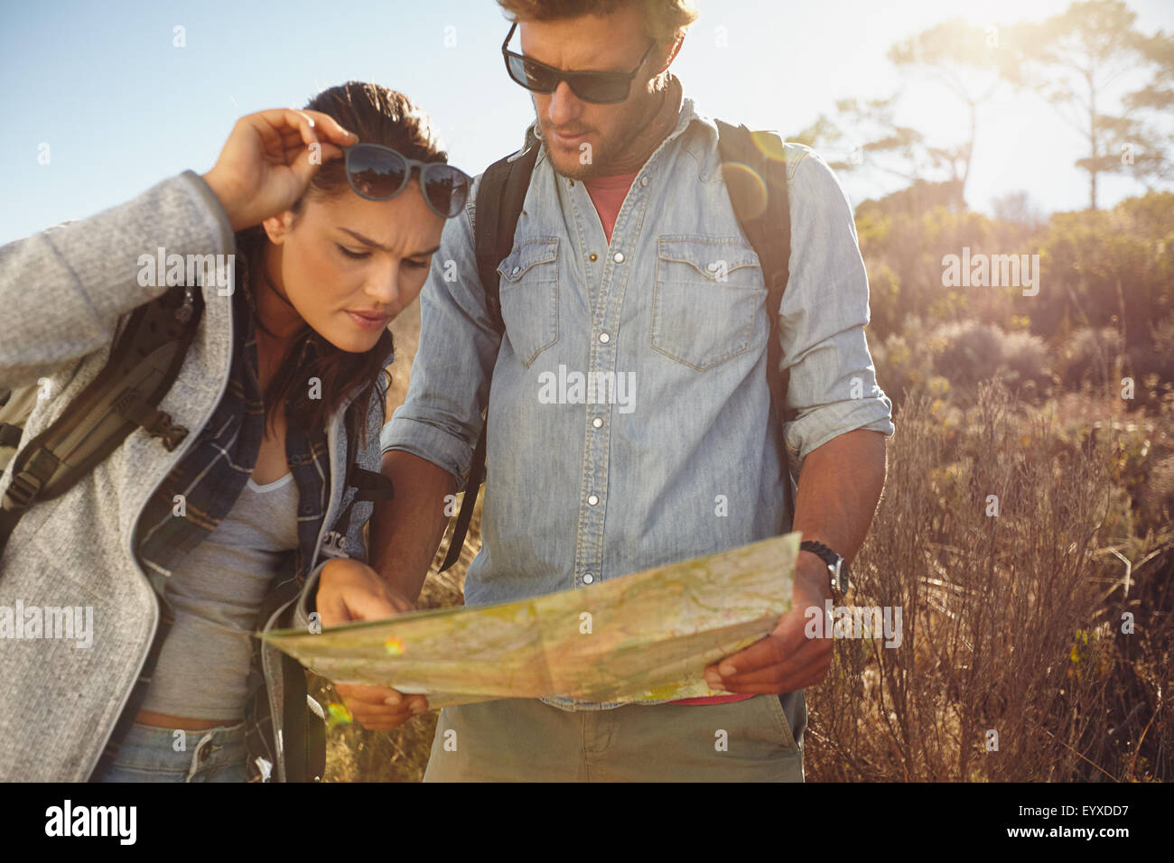 Hikers looking at map. Couple navigating together during travel hike outdoors in countryside. - Stock Image