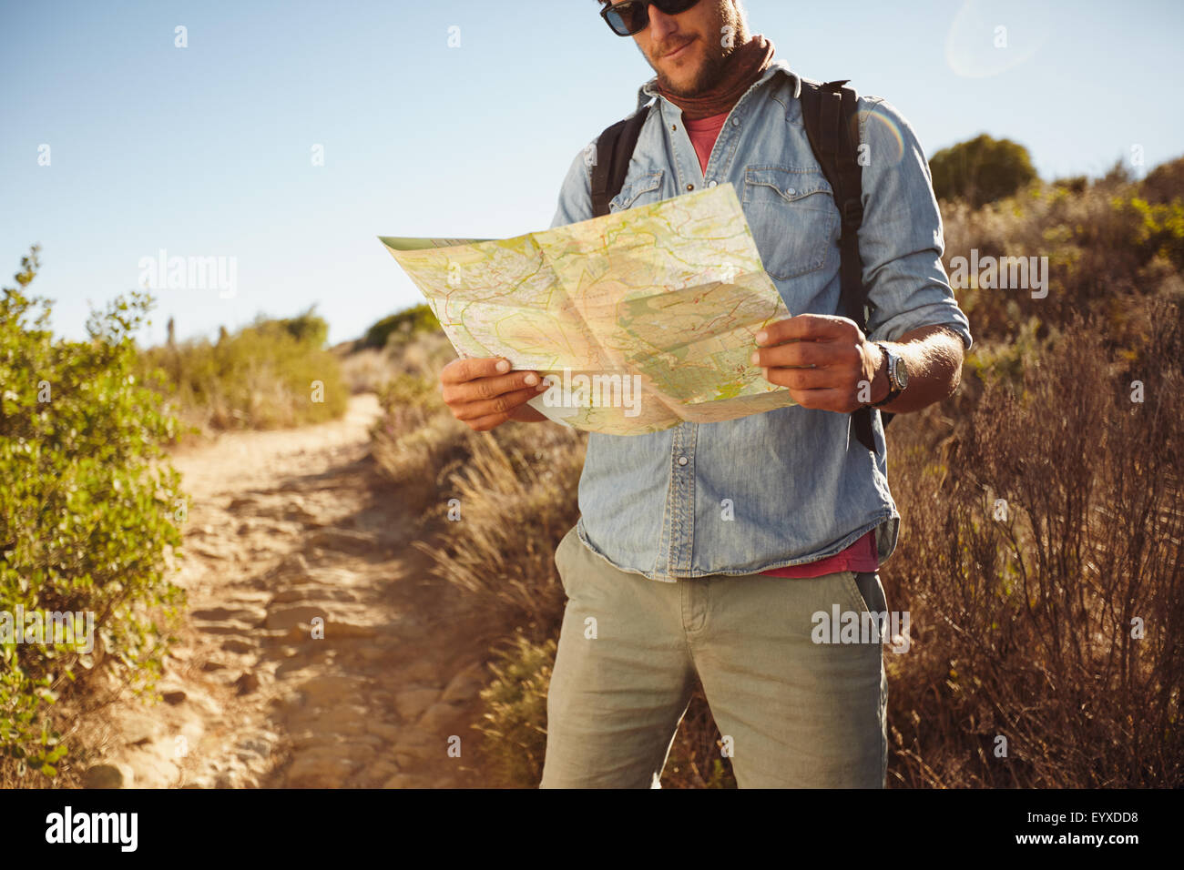 Shot of a man in countryside with a map, figuring out his orientation. Male hiker hiking in country. - Stock Image