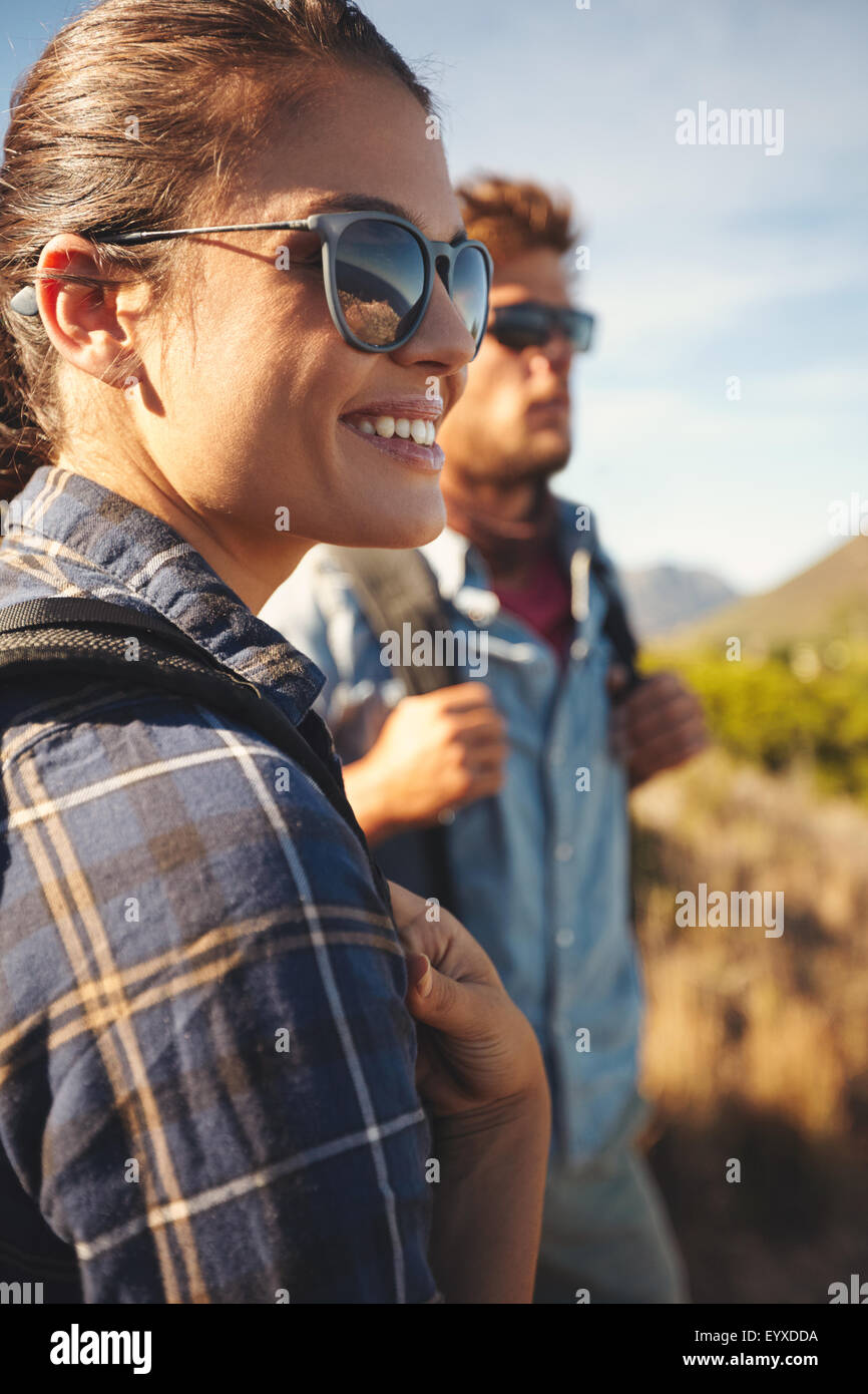 Close up image of young woman looking away smiling with young man in background. Hiker couple enjoying summer vacation - Stock Image