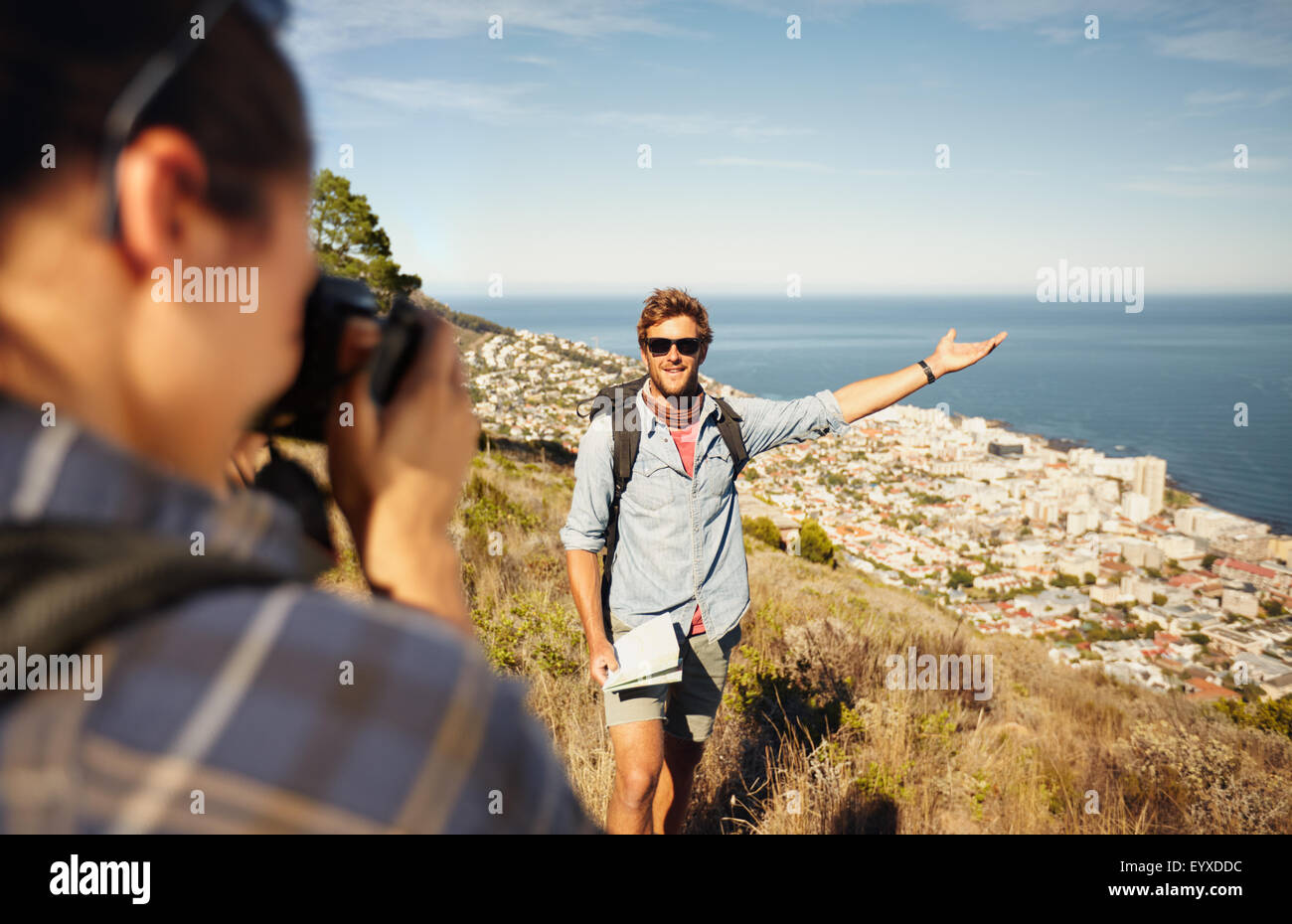Outdoor shot of tourist couple enjoying nature and taking photo. Woman taking picture of boyfriend showing something - Stock Image