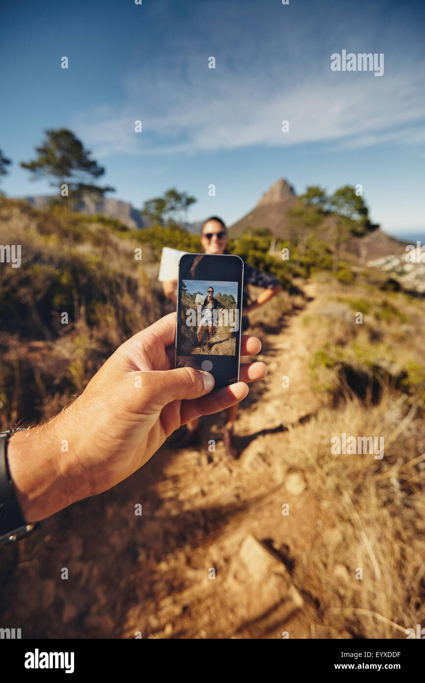 Man talking pictures of a woman holding a man with mobile phone. focus on smart phone and hand. Couple on hiking - Stock Image