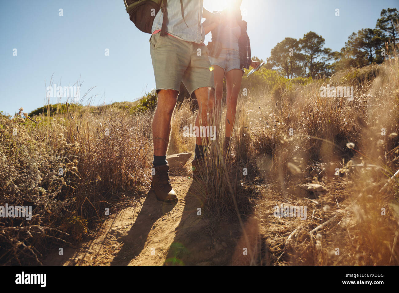 Low angle view of man and woman hikers walking on dirt trail on mountain on a sunny day. Couple hiking in nature. - Stock Image