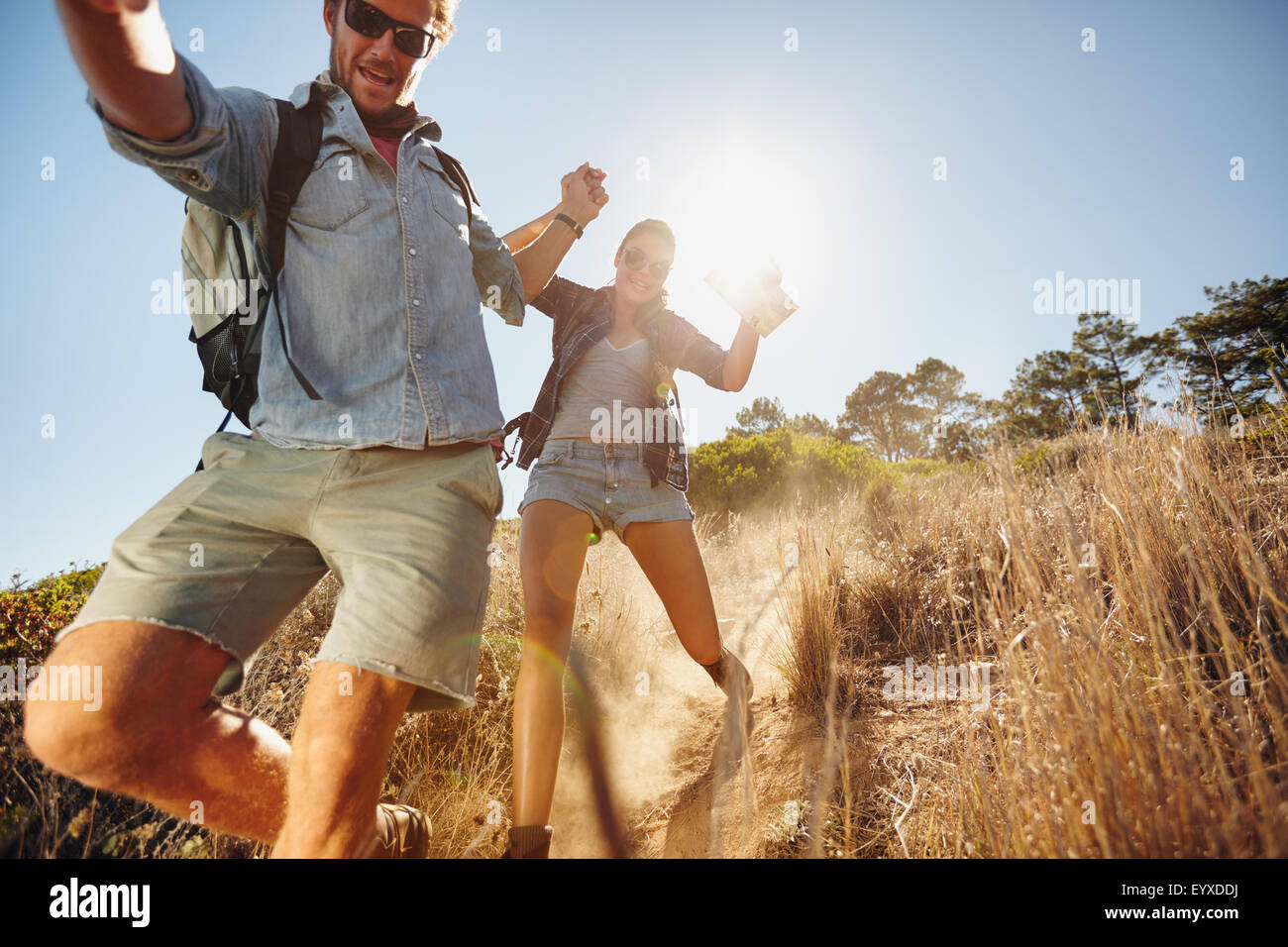 Portrait of happy young couple having fun on their hiking trip, sliding down the mountain trail. Caucasian hiker - Stock Image