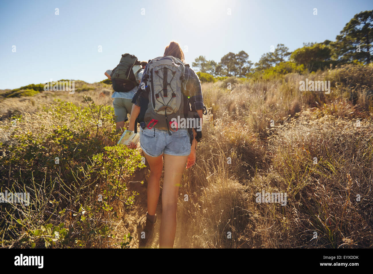Rear view of couple of young people hiking. Young man and woman hiking going uphill on mountain on summer day. - Stock Image