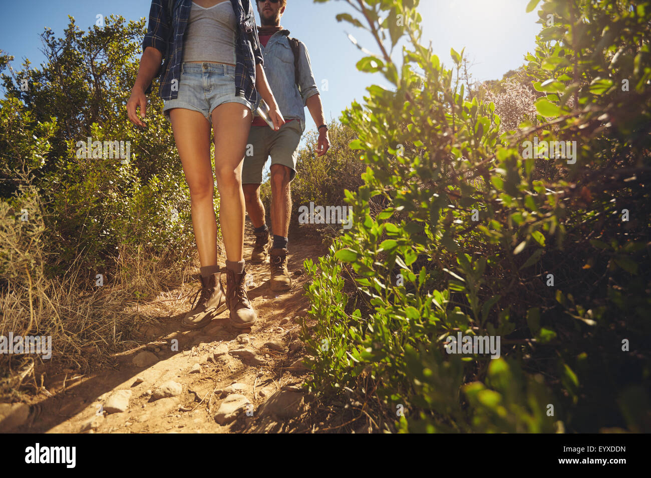 Hikers walking through country trail. Two young people hiking on mountains on sunny day. Cropped shot focus on legs. - Stock Image