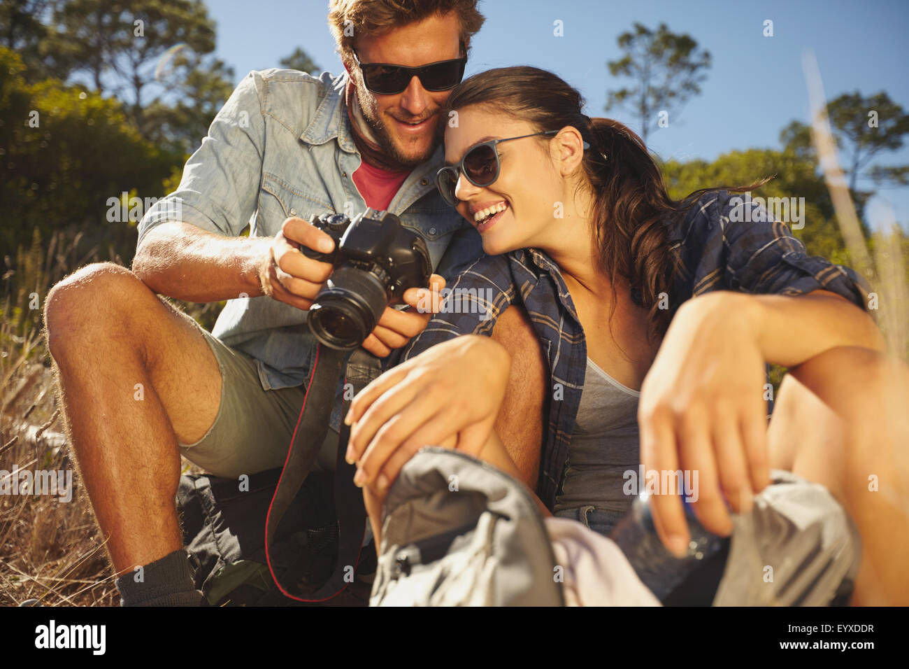Hiker couple looking taken picture on digital camera during journey outdoor on vacation. Smiling couple taking a - Stock Image